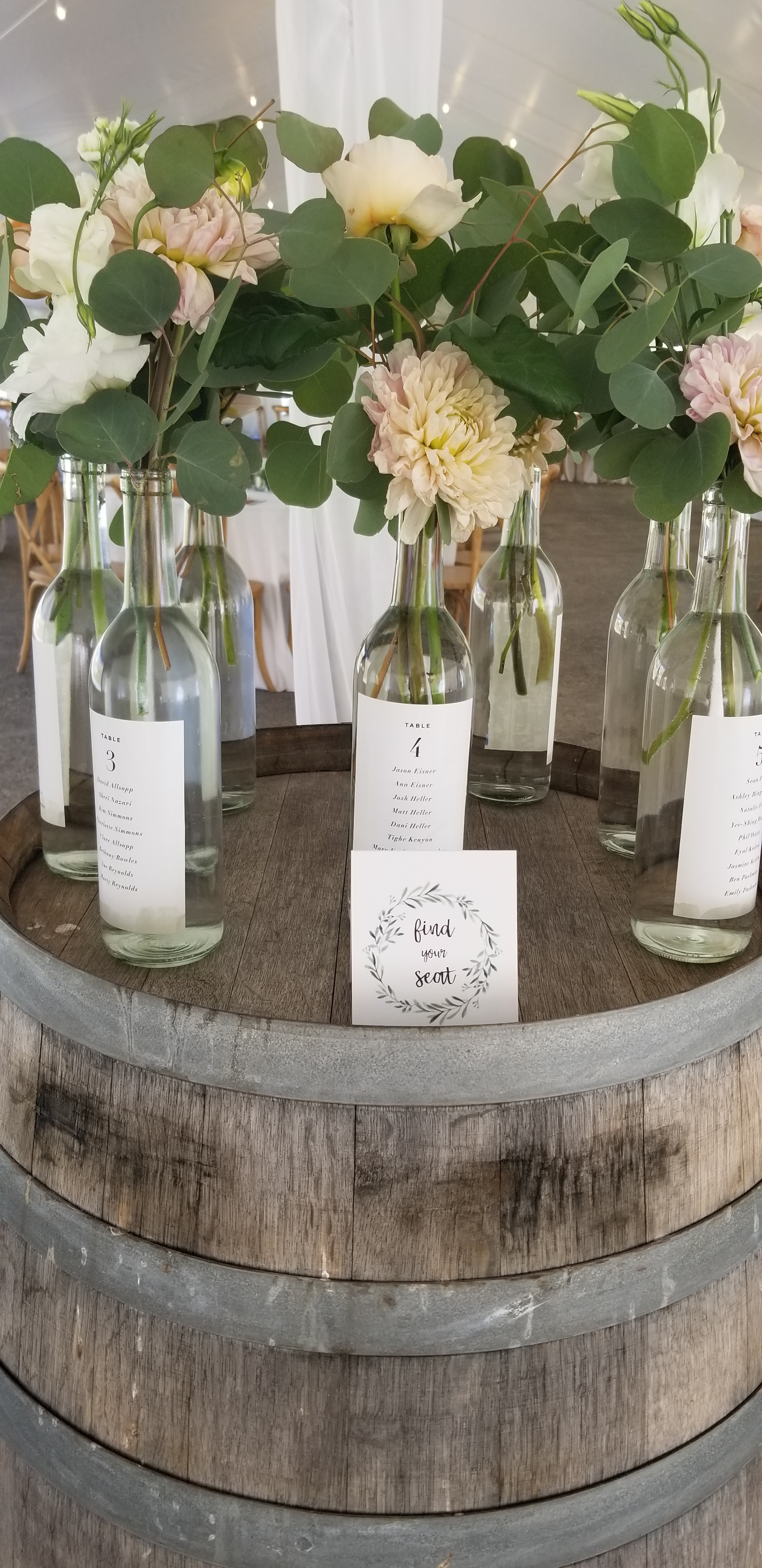 Seating chart presented in wine bottles with lush floral.