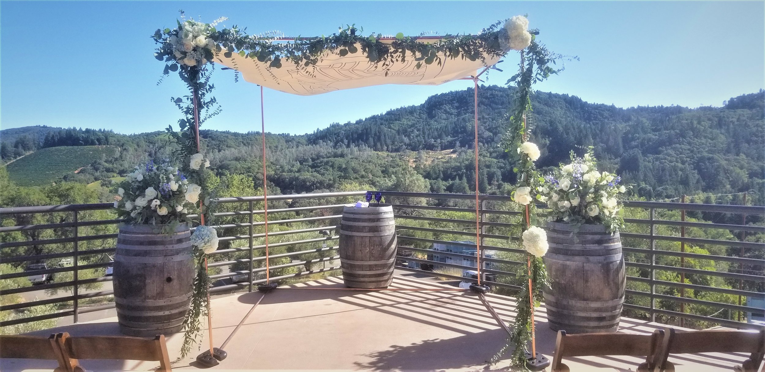 Chuppah floral and greenery, flowing Italian ruscus and eucalyptus, flowers in white and blue at the terrace at Sbragia winery in Geyserville