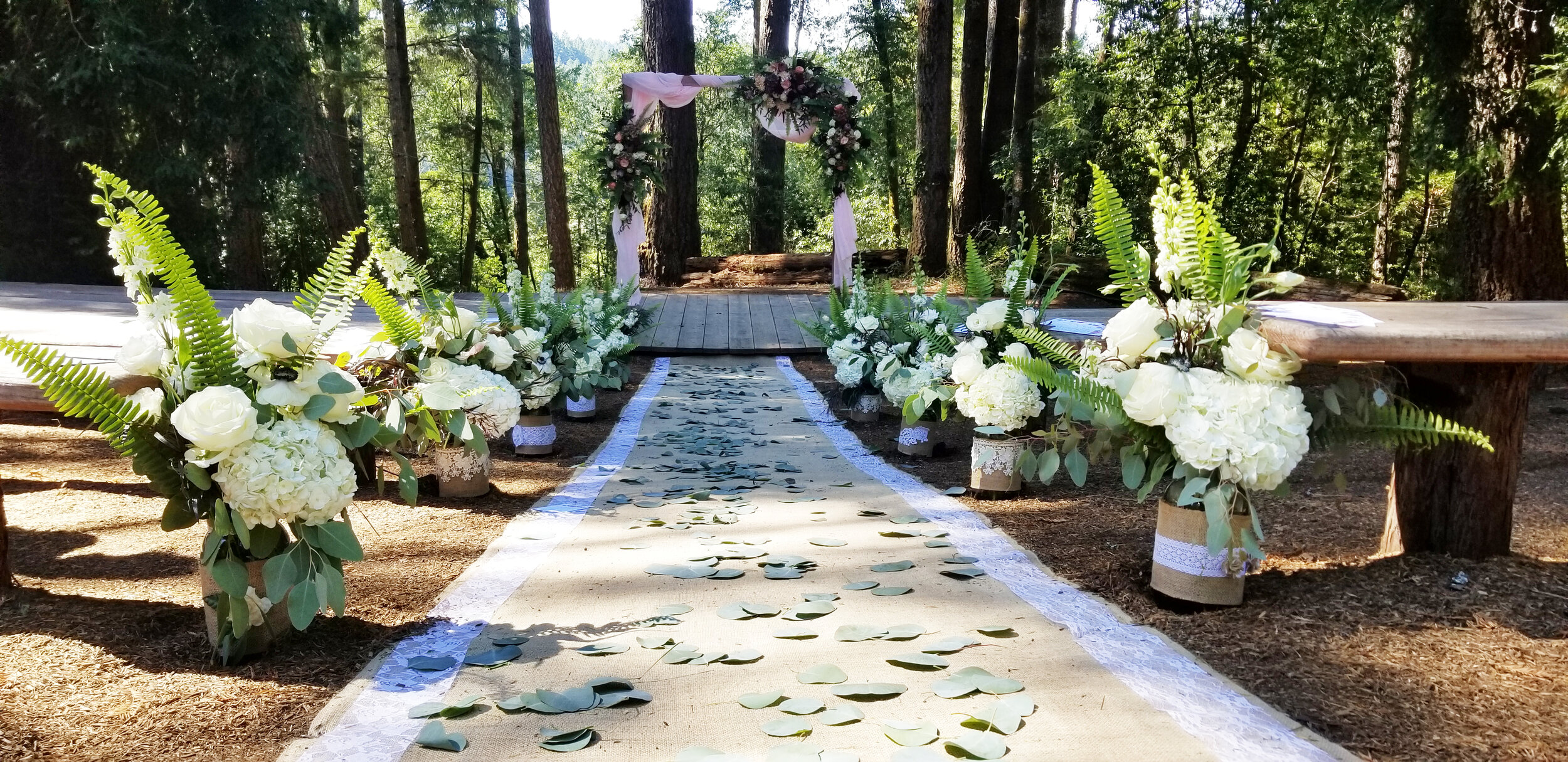 Wedding Aisle runner in eucalyptus lined with lush floral. Perfect Redwood grove wedding flowers