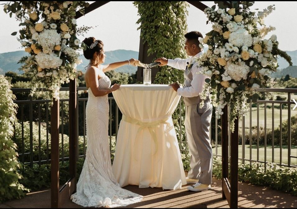 Ceremony arch, full white and yellow flowers at Stone Tree Golf Course