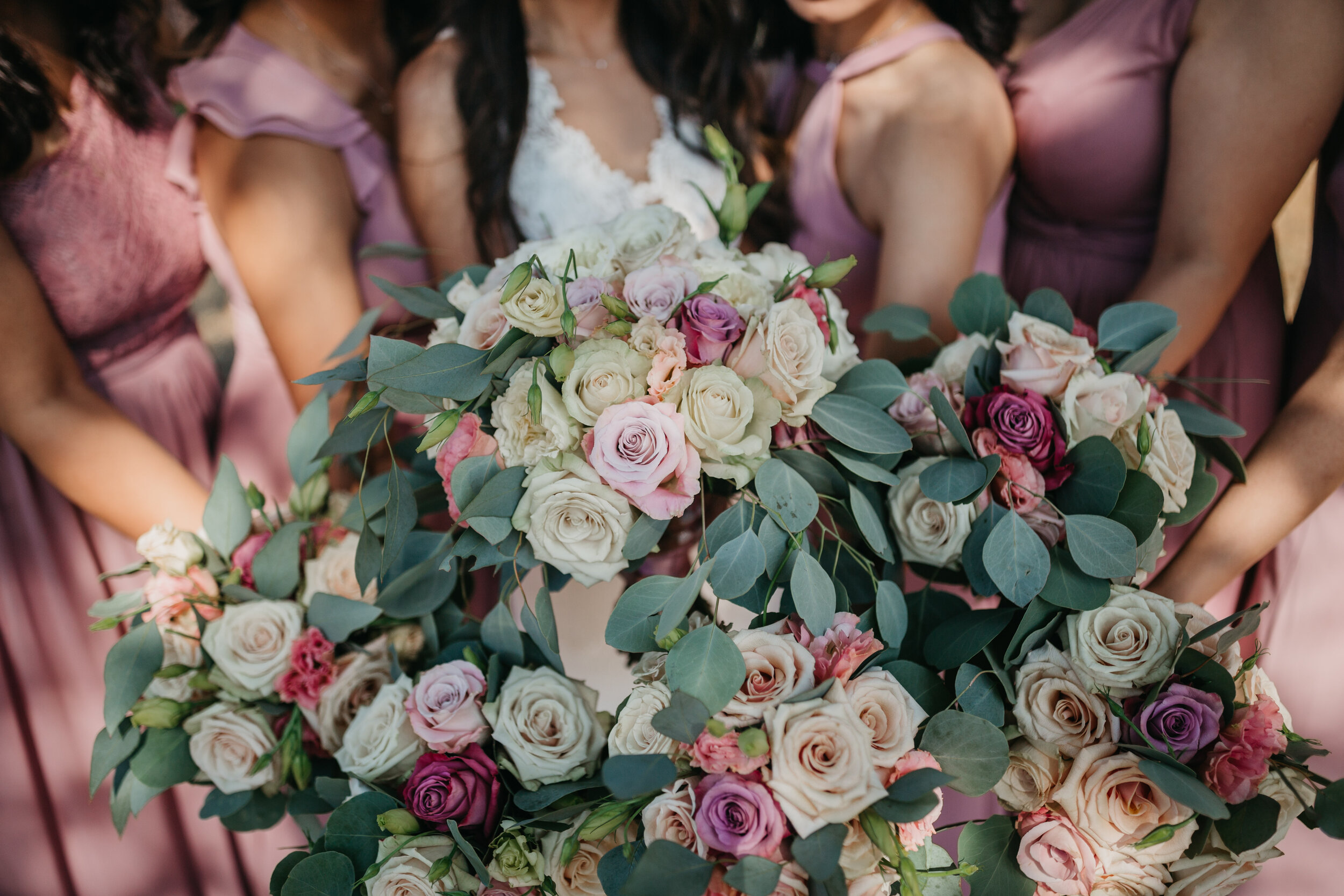 Bride and Maids, bouquets in leafy green eucalyptus with mauve, blush and white flower.  Photo by @whitneyjustesenphoto