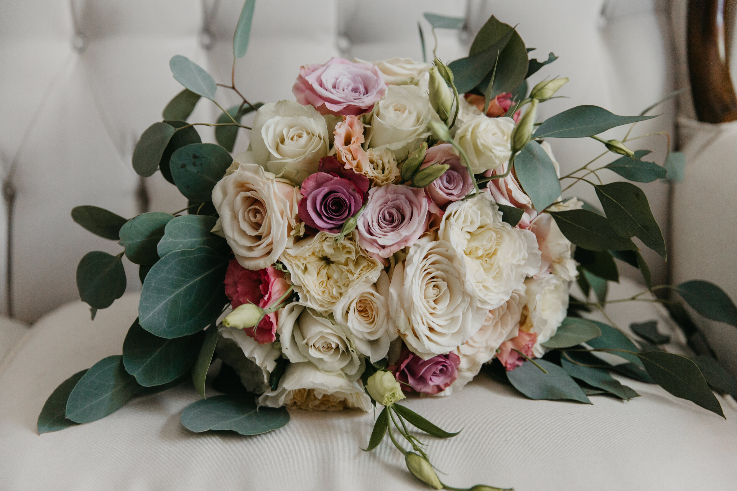 Mauve, blush and white English roses, ranunculus and lisianthus in a flowing eucalyptus bouquet