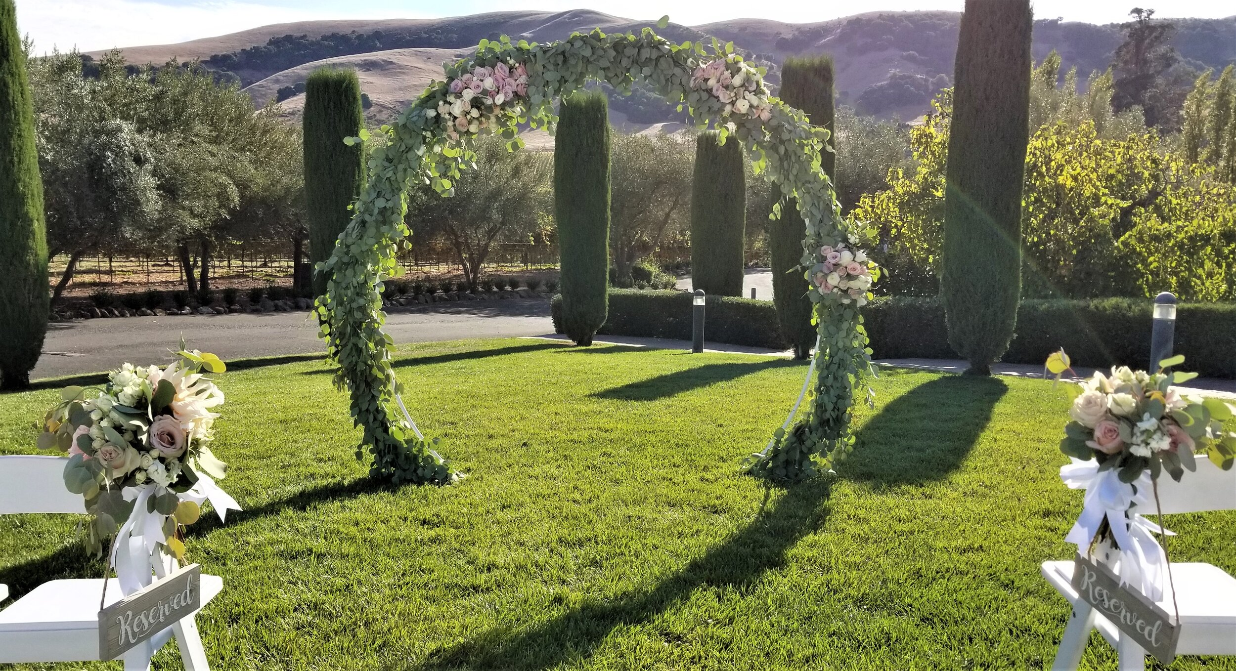 Circular Arch, Green garland with clusters of mauve, blush and white fresh flowers. Viansa Winery, Sonoma