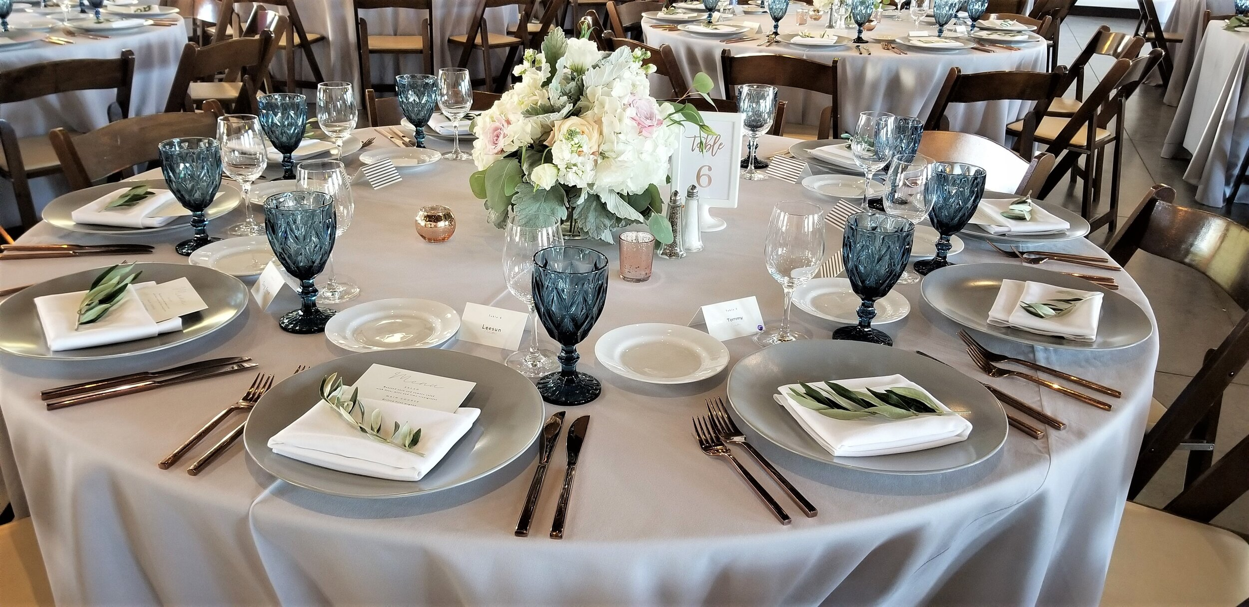 Round guest table centerpiece at Viansa Winery in Sonoma. Mauve, blush and white flowers, olive sprigs on each place setting.