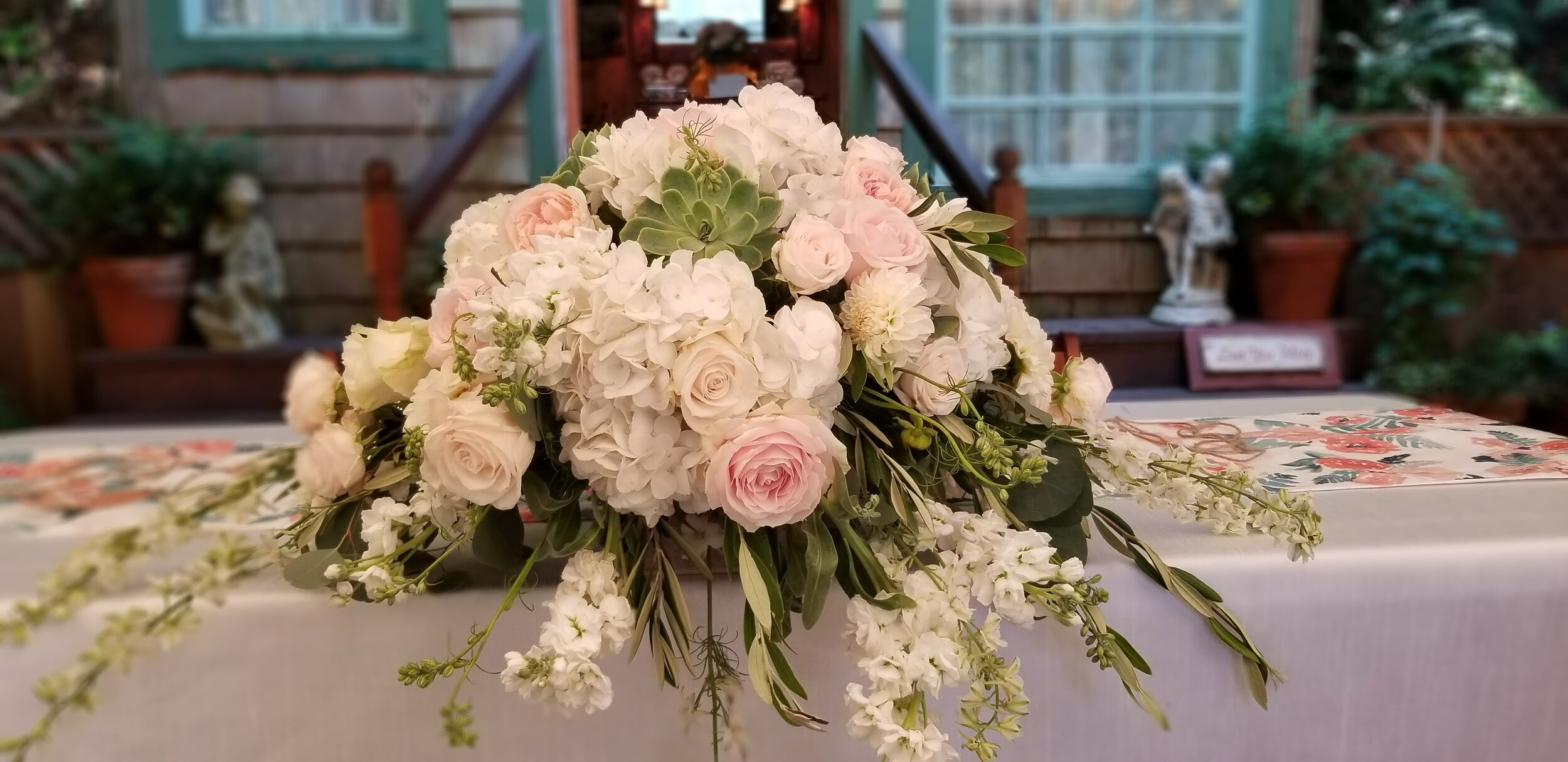 Sweetheart table flowers, lush pink, blush and white with succulent accents, placed on the edge. Secret Gardens Bodega Bay.