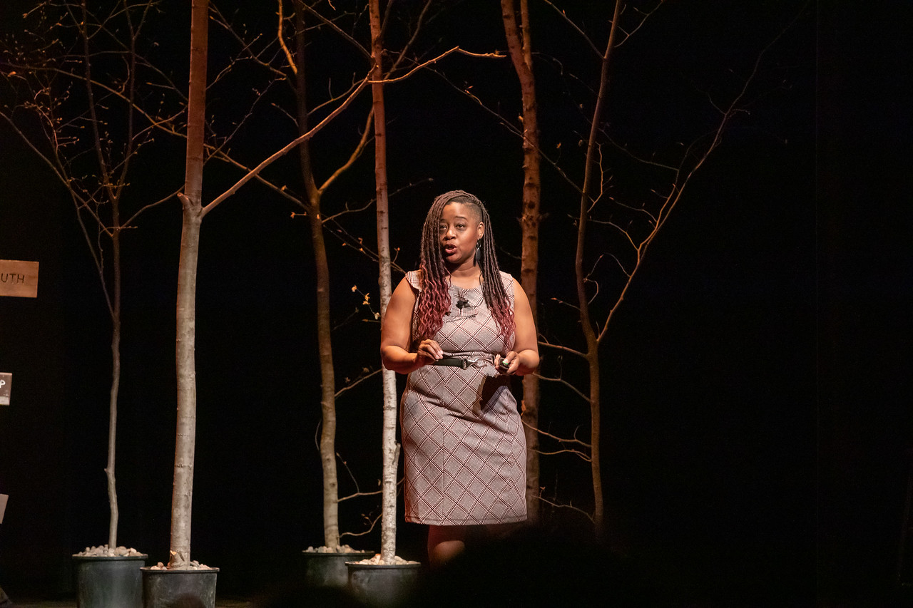 Photo Credit: Jesse Schloff Photography {Picture of Kiah on the TEDxStowe stage. She is spotlit against a dark background with trees as scenery just behind her.]