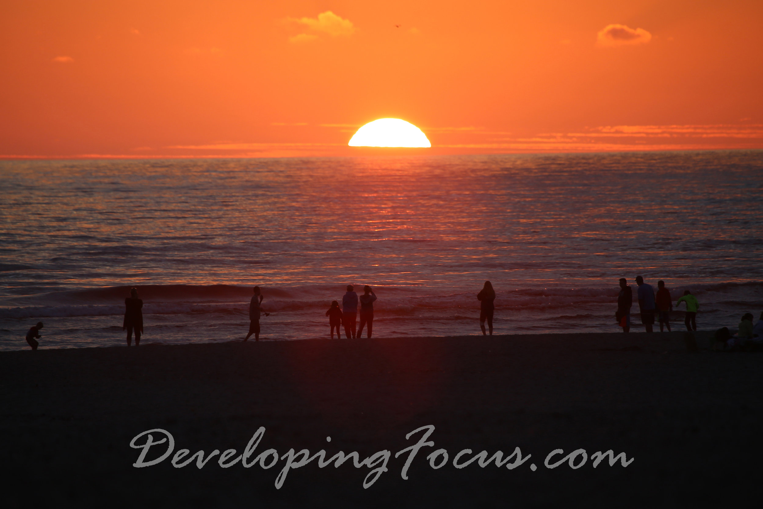 Beach-goers gather on the shoreline to watch the sunset at Sea Side, OR.