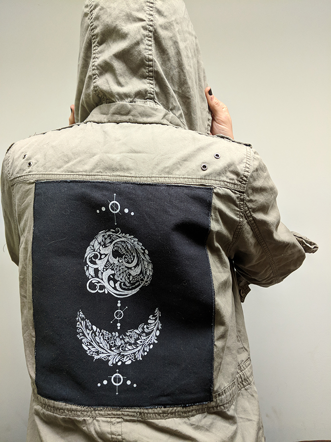 Slant Press homepage image featuring a screen printed pactch affixed to the back of a green military jacket.