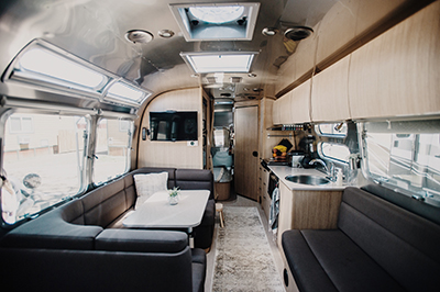 Airstreams are designed to let in tons of natural light, making everything feel spacious and open. We also really enjoy the subtle reflections on the aluminum ceiling.  Photo by Tay and McKay Photography