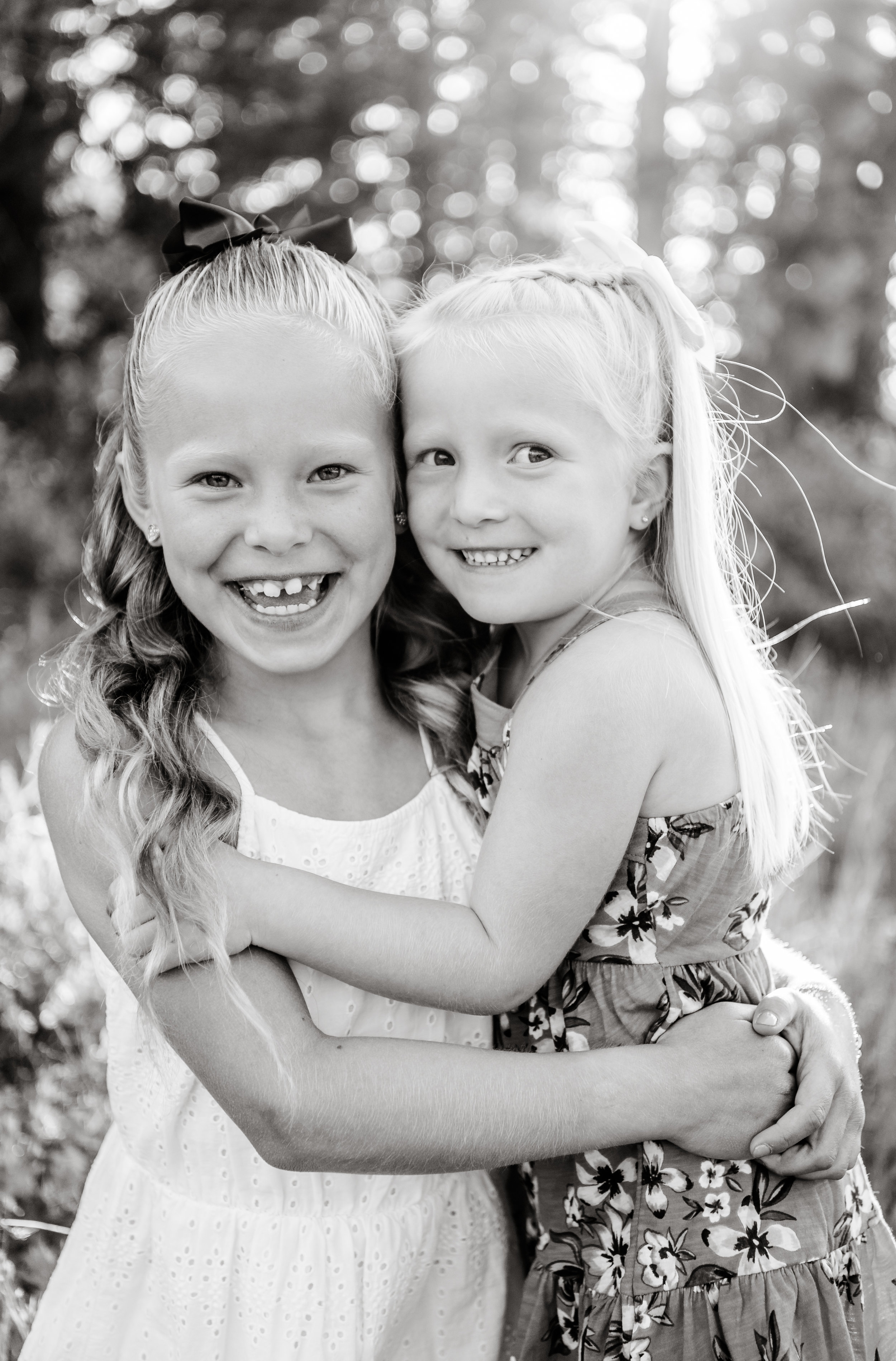 Sister's hugging during family pictures taken in Big Cottonwood Canyon in July.