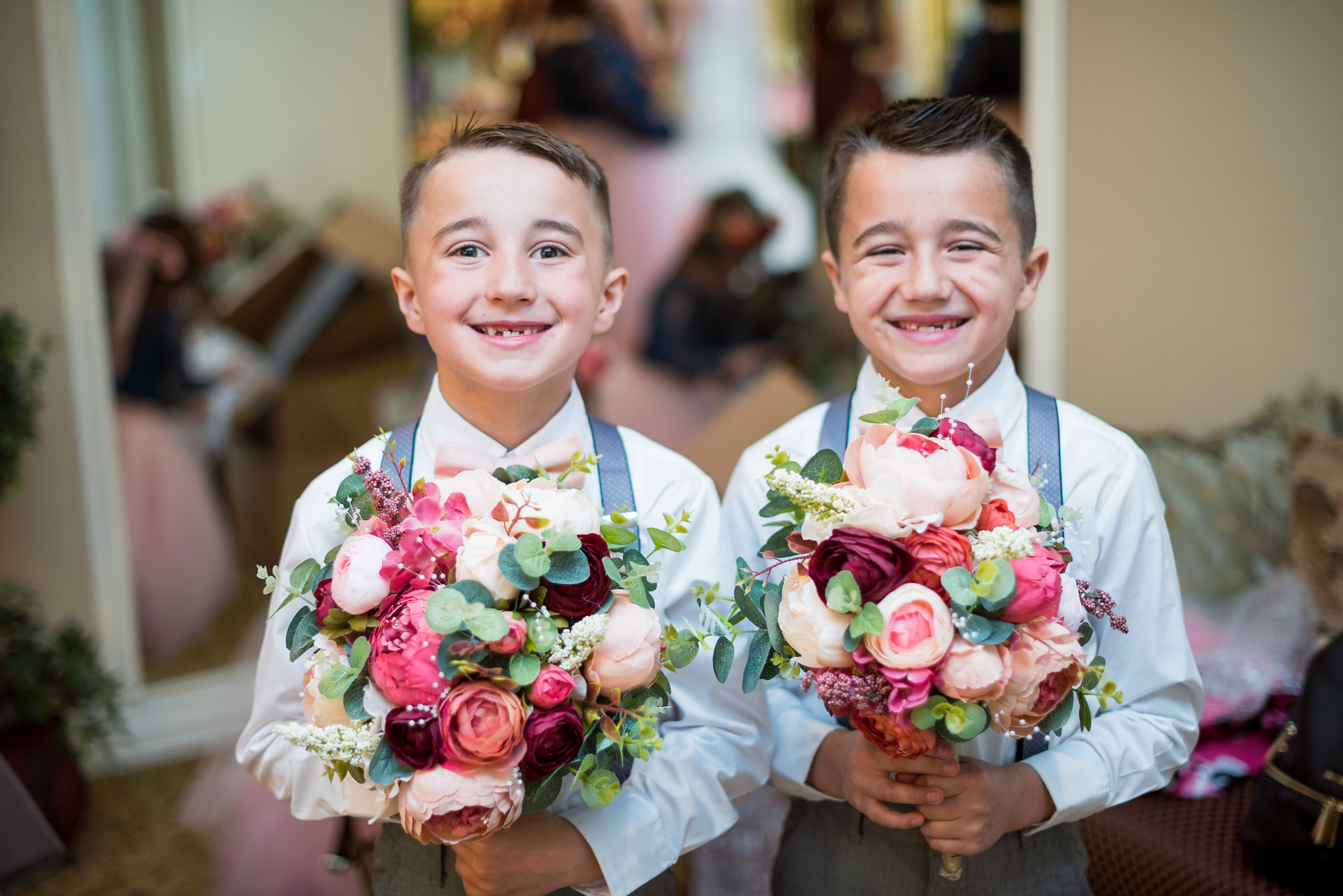 Ring Bearers at the ready to help the bridesmaids with anything they may need! Including holding their flowers for them.