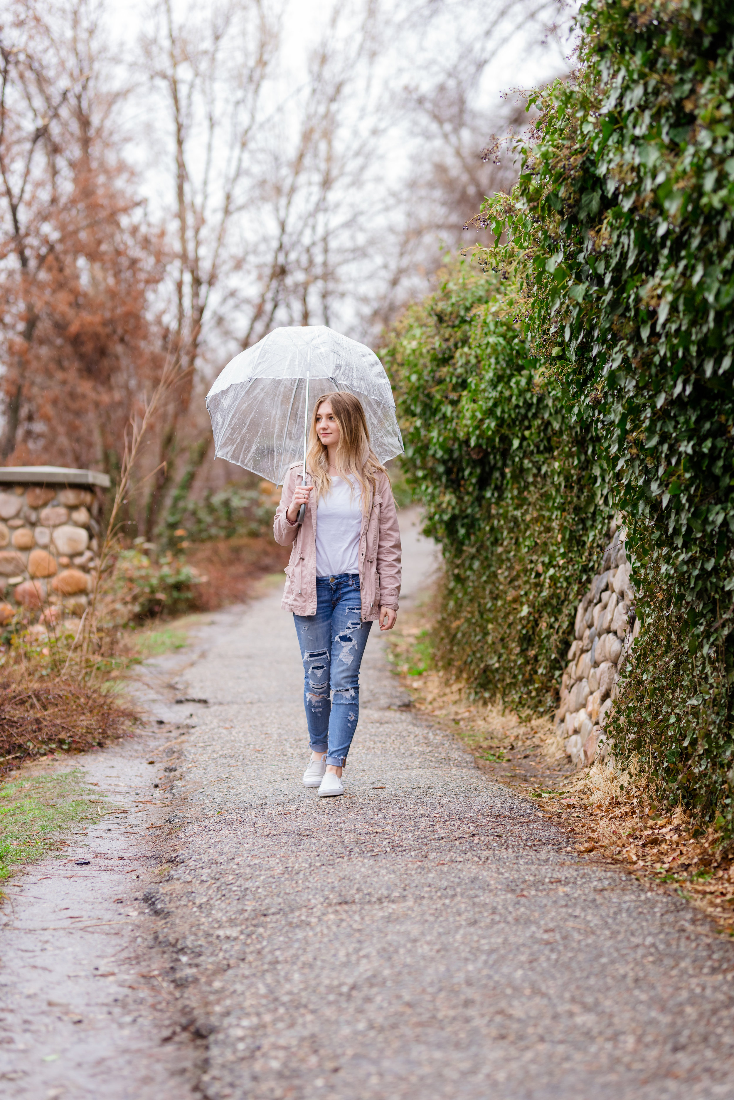 Walking through the rain with a smile and an umbrella. Rainy Day Senior girl pictures in the rain at Memory Grove Park in Downtown Salt Lake City.
