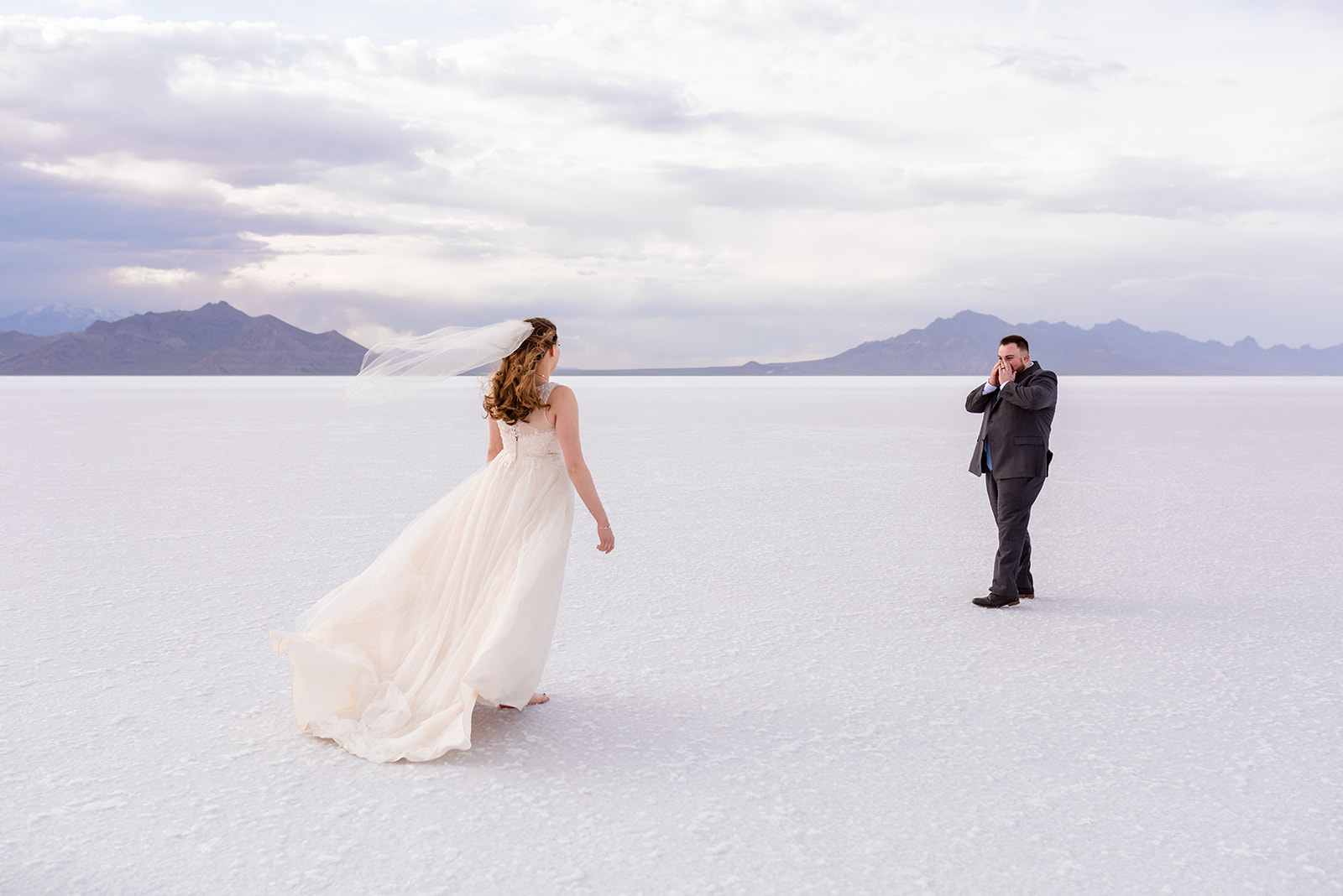 Zach's first reaction to seeing his bride to be. Groom reaction during first look at the Bonneville Salt Falts in Utah taken by Coley Cook Photography.