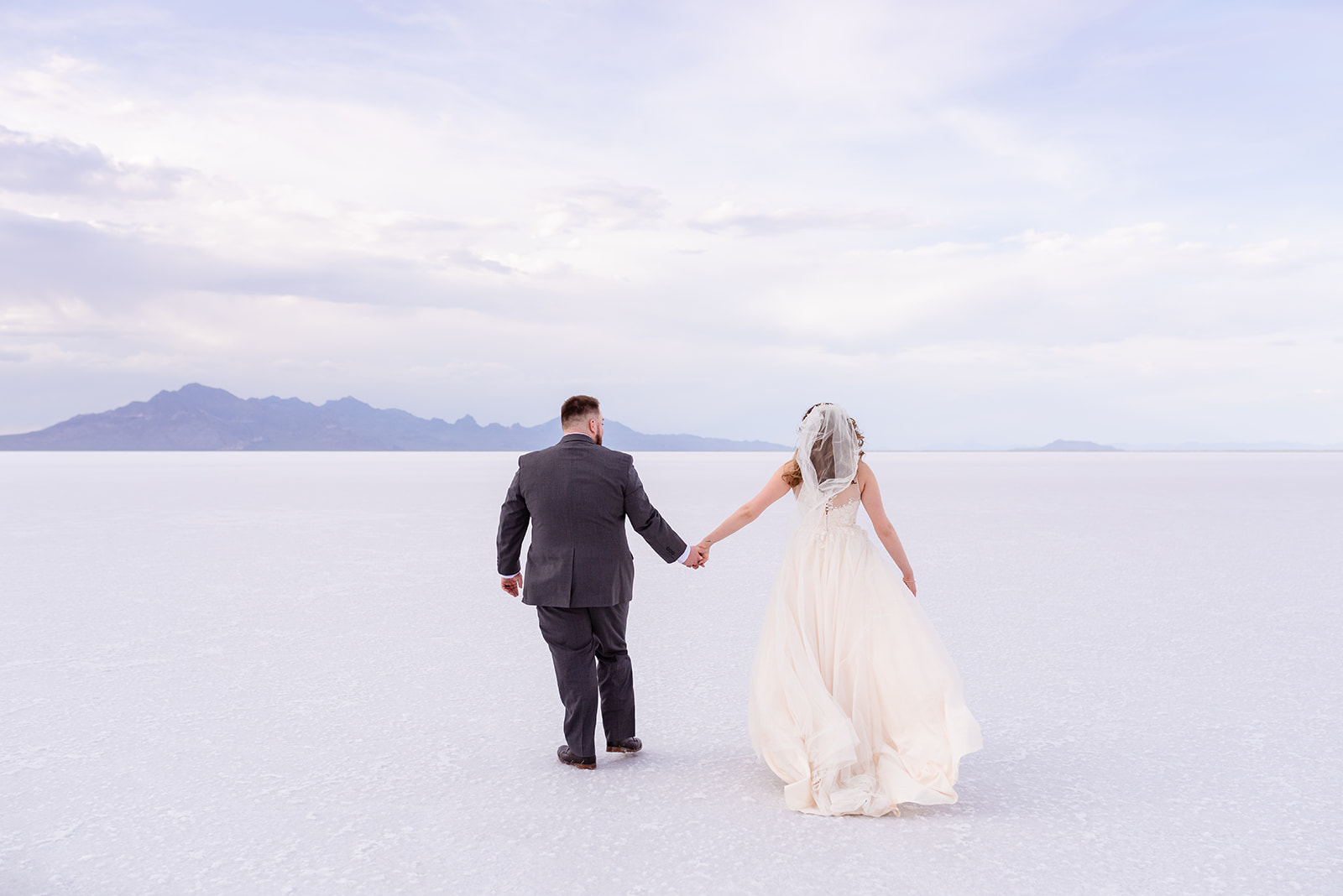 Walking hand in hand as bride and groom at the Bonneville Salt Falts in Utah. Taken by Coley Cook Photography.