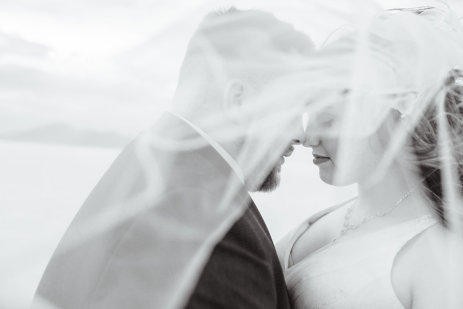 Romantic veil shot of our Utah bride and groom at the Bonneville Salt Falts in Utah. Taken by Coley Cook Photography.