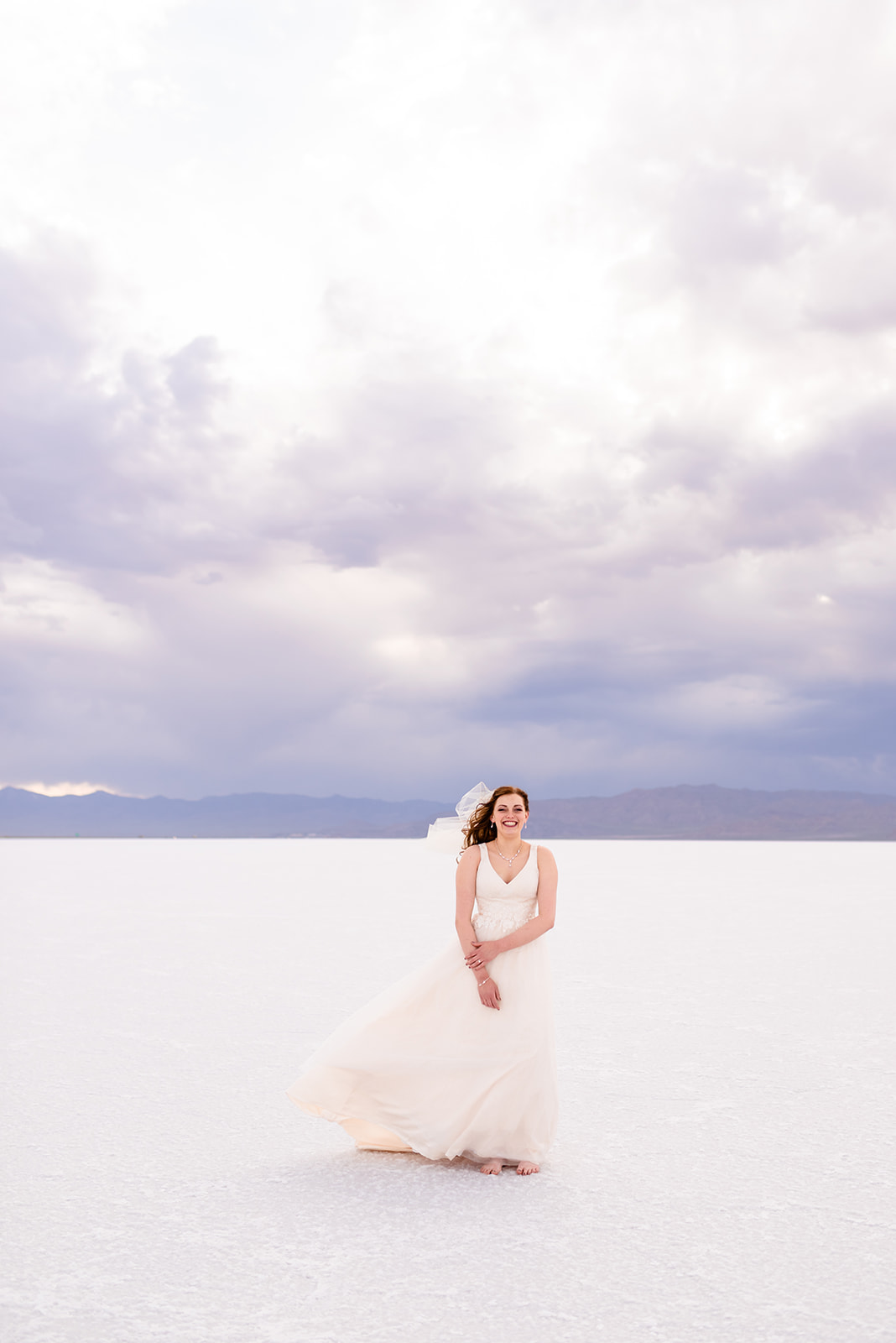 Laughing bridal portrait of Adri at the Bonneville Salt Falts in Utah. Taken by Coley Cook Photography.