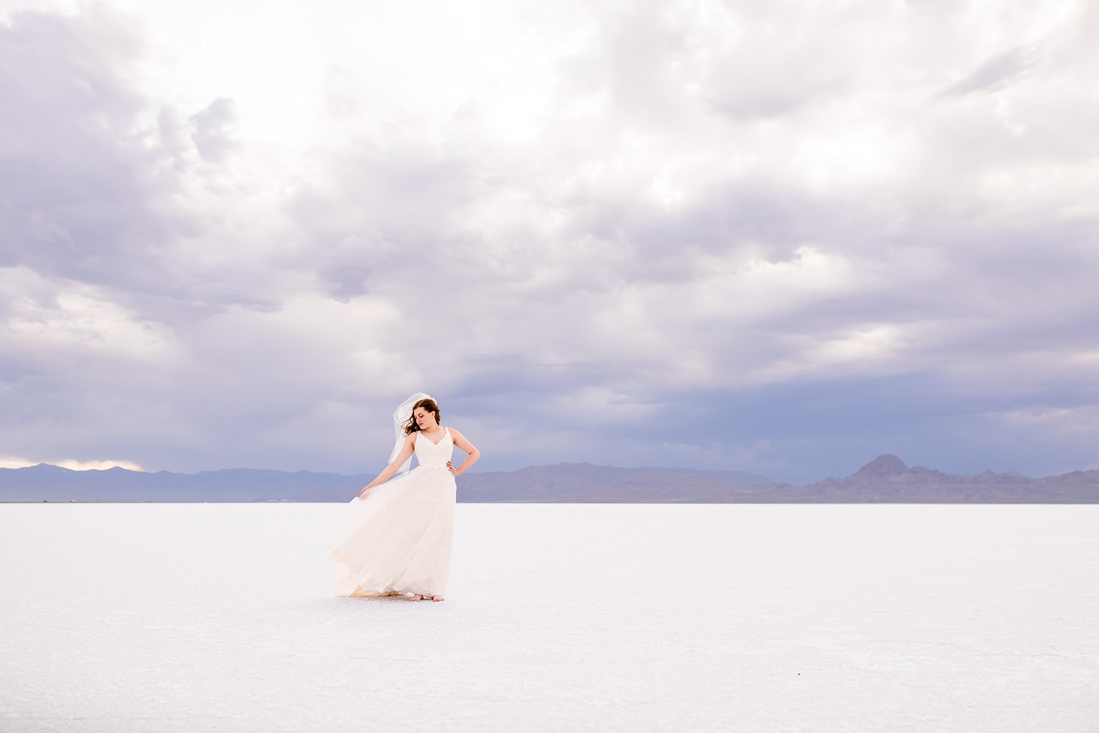Romantic bridal portrait of Adri at the Bonneville Salt Falts in Utah. Embrace the wind! Taken by Coley Cook Photography.