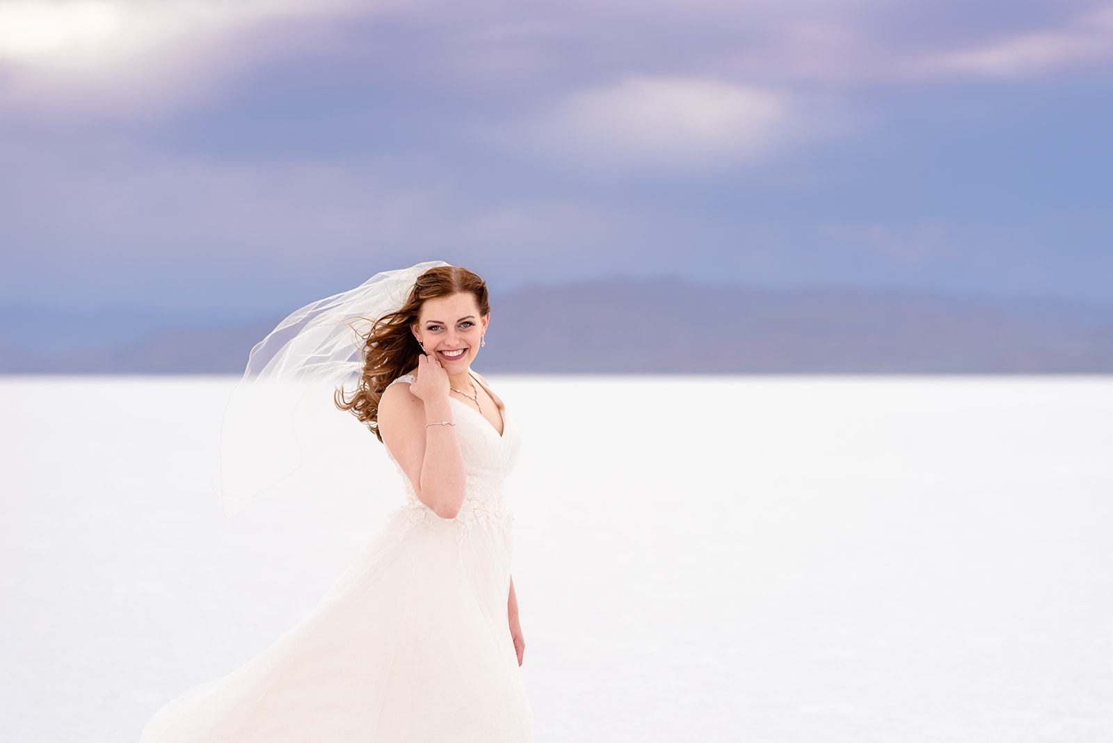 Smiling bridal portrait of Adri at the Bonneville Salt Falts in Utah. Embrace the wind! Taken by Coley Cook Photography.