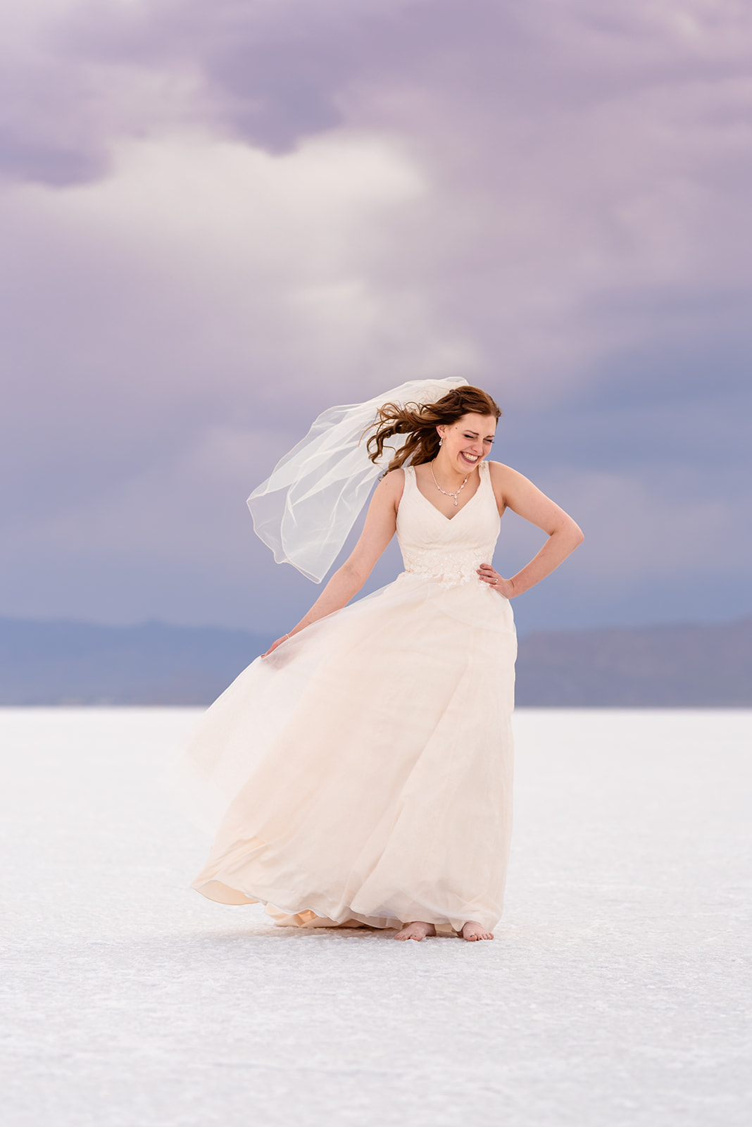 Laughing bridal portrait of Adri at the Bonneville Salt Falts in Utah. Embrace the wind! Taken by Coley Cook Photography.