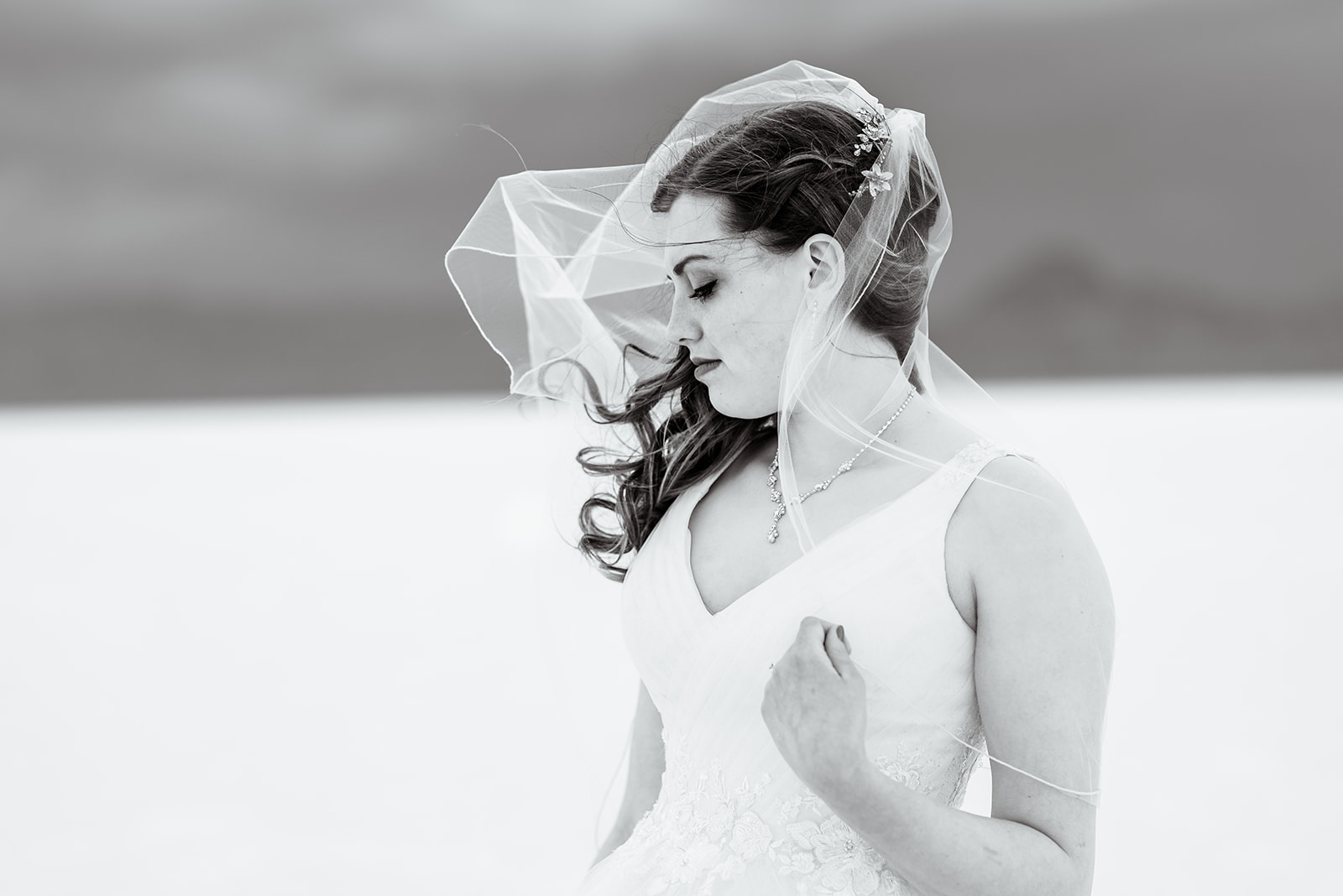 Romantic black and white bridal portrait of Adri at the Bonneville Salt Falts in Utah. Embrace the wind! Taken by Coley Cook Photography.