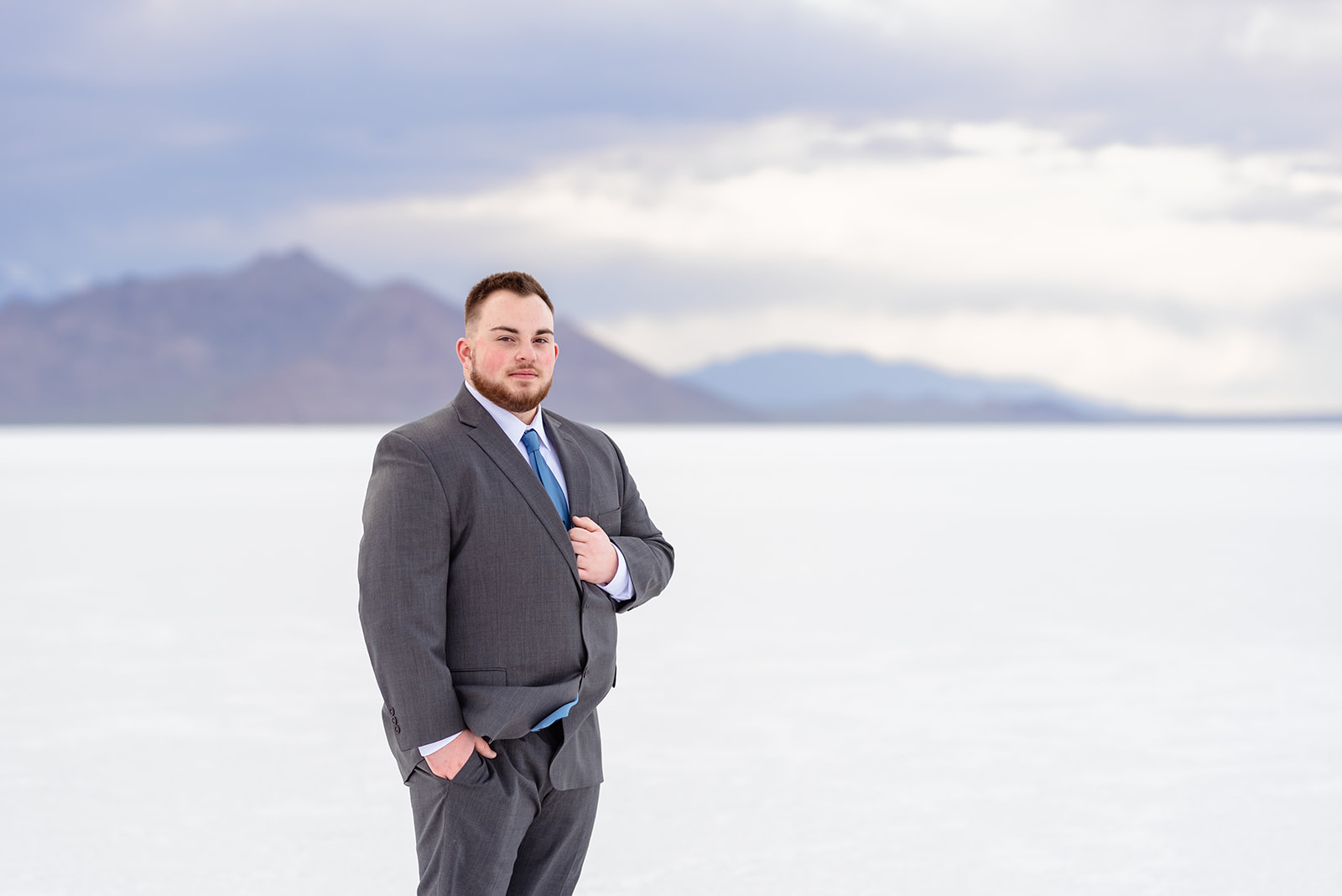 Classic groom portrait of Zach at the Bonneville Salt Falts in Utah. Grey suit and blue tie combo. Taken by Coley Cook Photography.