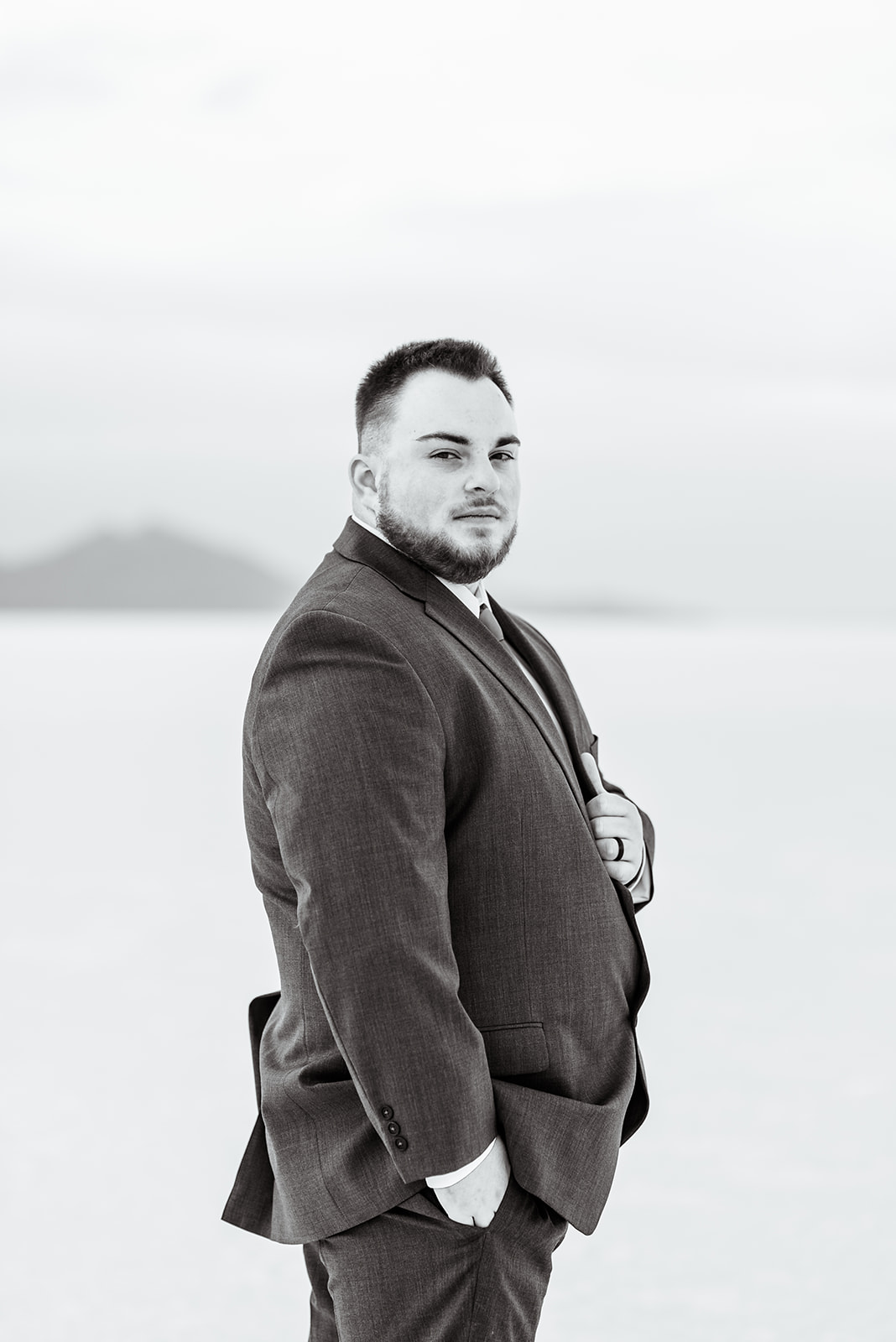 Classic black and white groom portrait of Zach at the Bonneville Salt Falts in Utah. Grey suit and blue tie combo. Taken by Coley Cook Photography.