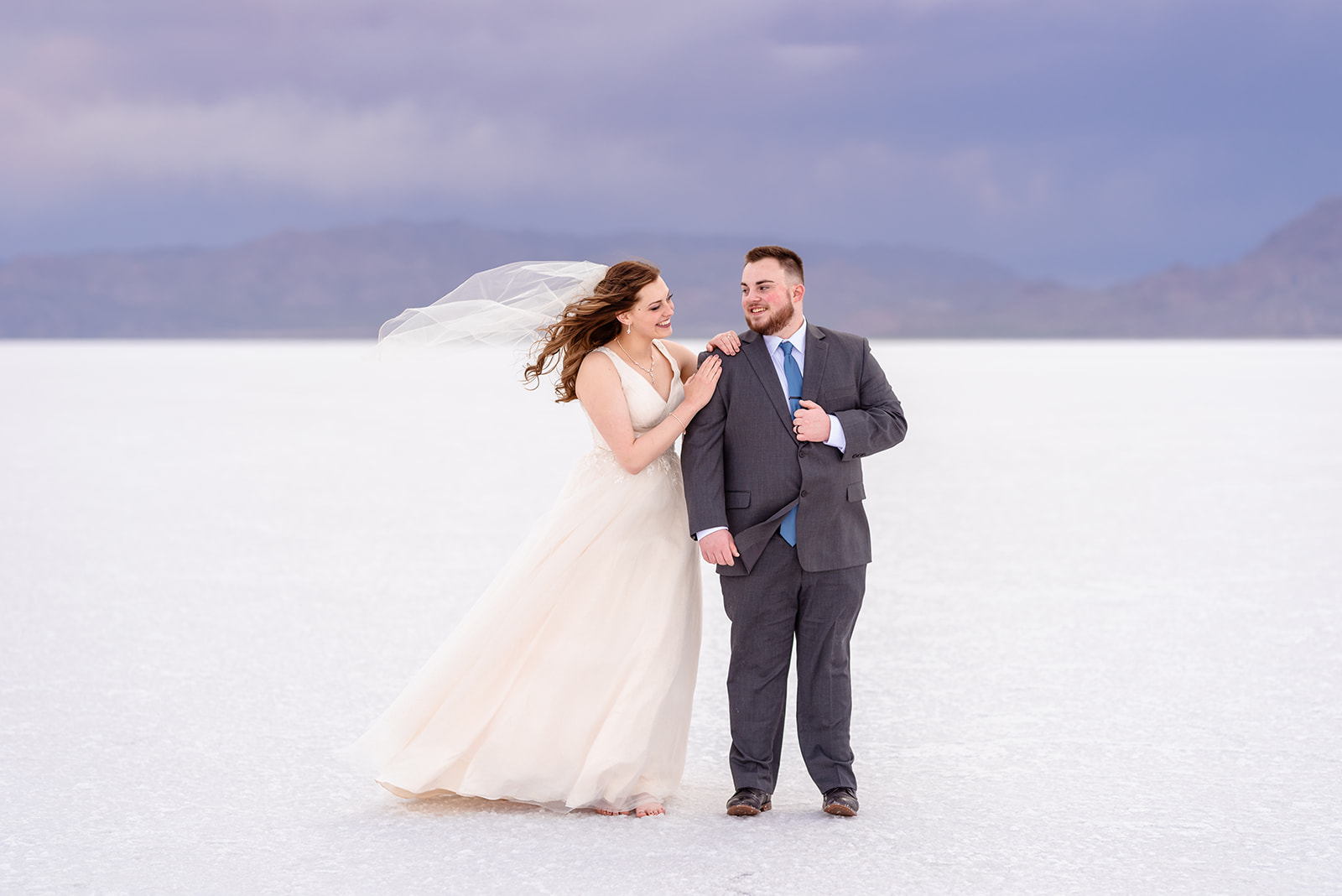 Bride and Groom portraits at the Bonneville Salt Falts in Utah. Grey suit and blue tie combo. Ivory and Gold wedding dress. Taken by Coley Cook Photography.