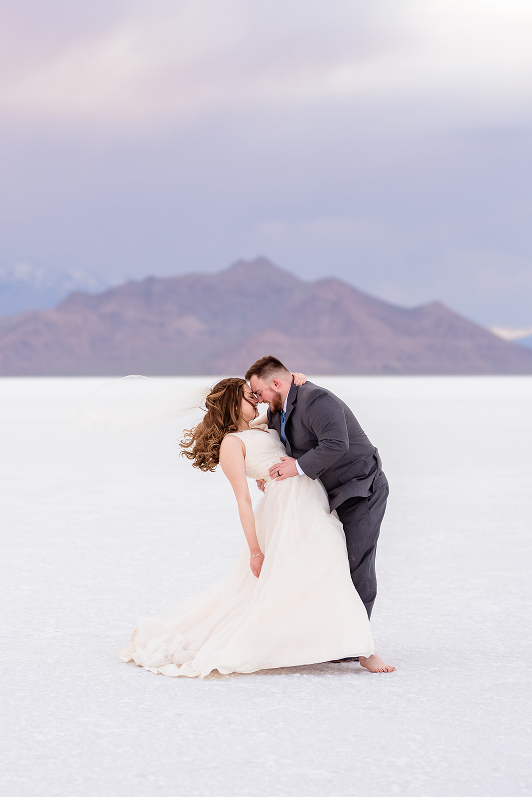 Bride and Groom dipping portraits at the Bonneville Salt Falts in Utah. Grey suit and blue tie combo. Ivory and Gold wedding dress. Taken by Coley Cook Photography.