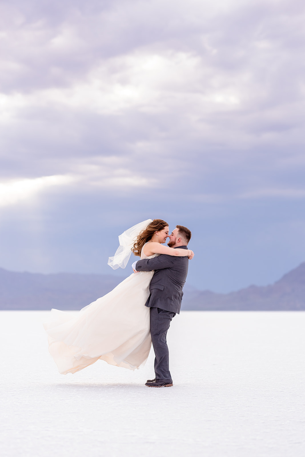 Bride and Groom pick me up pose portraits at the Bonneville Salt Falts in Utah. Grey suit and blue tie combo. Ivory and Gold wedding dress. Taken by Coley Cook Photography.
