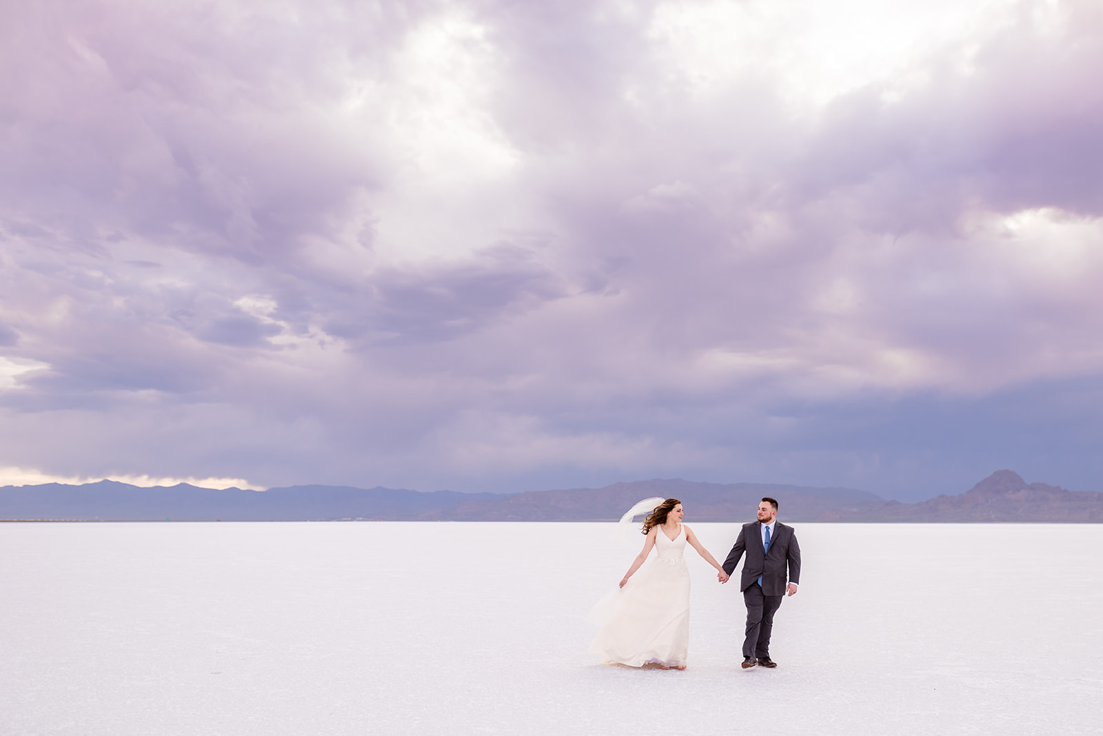 Bride and Groom walking portraits at the Bonneville Salt Falts in Utah. Grey suit and blue tie combo. Ivory and Gold wedding dress. Taken by Coley Cook Photography. Walking through the stormy skies.