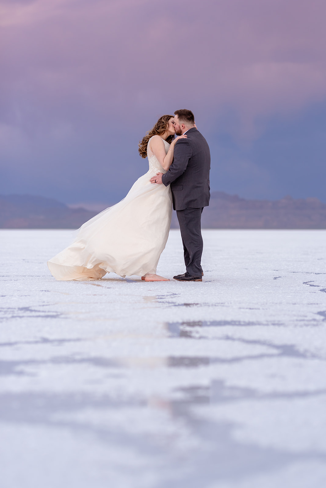 Bride and Groom portraits at the Bonneville Salt Falts in Utah. Stormy Sunset at the Salt Flats. Grey suit and blue tie combo. Ivory and Gold wedding dress. Taken by Coley Cook Photography.