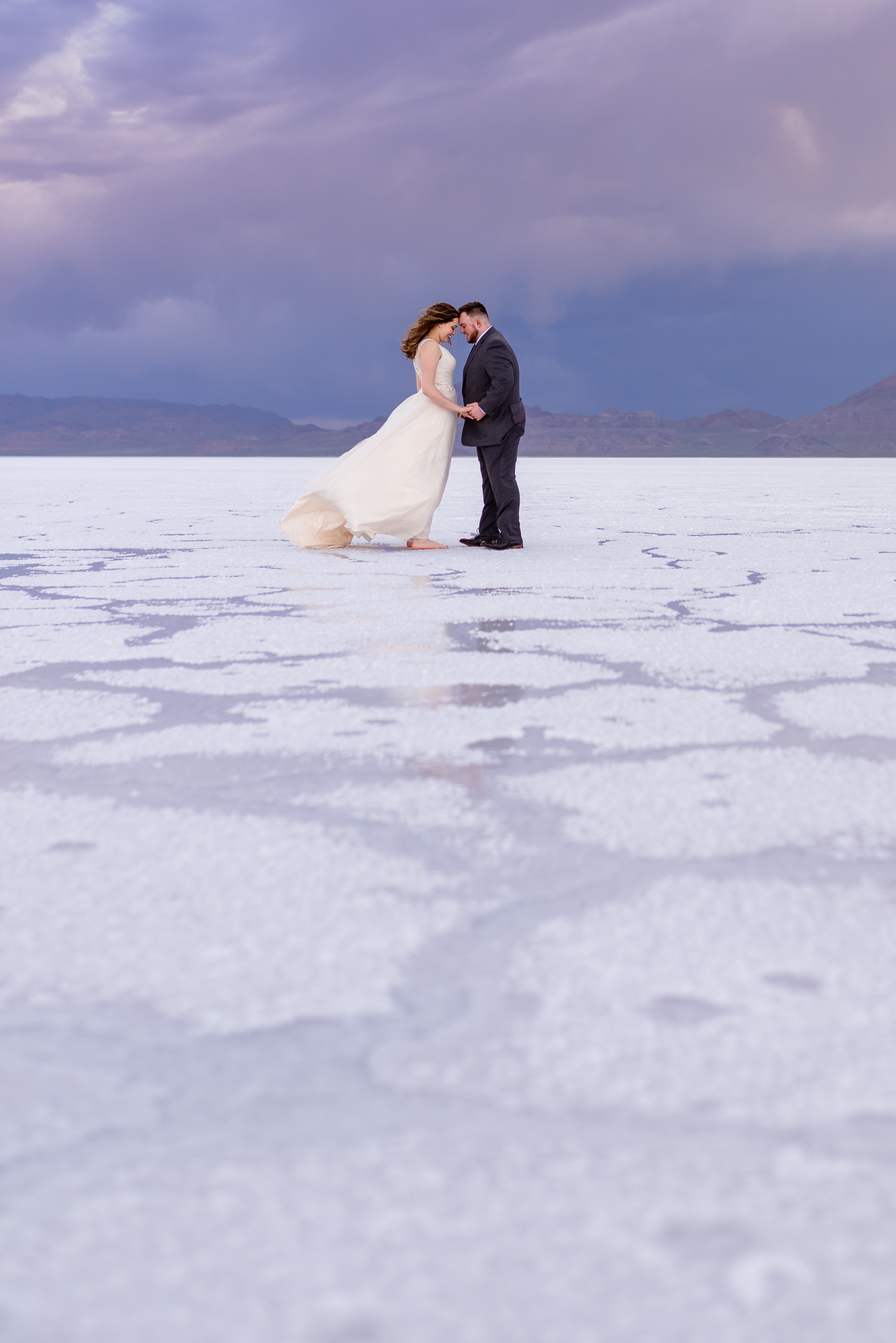 Loving Each other through the storms. Formals and first look wedding session taken at the Bonneville Salt Flats in Utah during a stormy evening in May. Gold and ivory wedding dress with groom's blue suit and purple tie. Images taken by Coley Cook Photography.