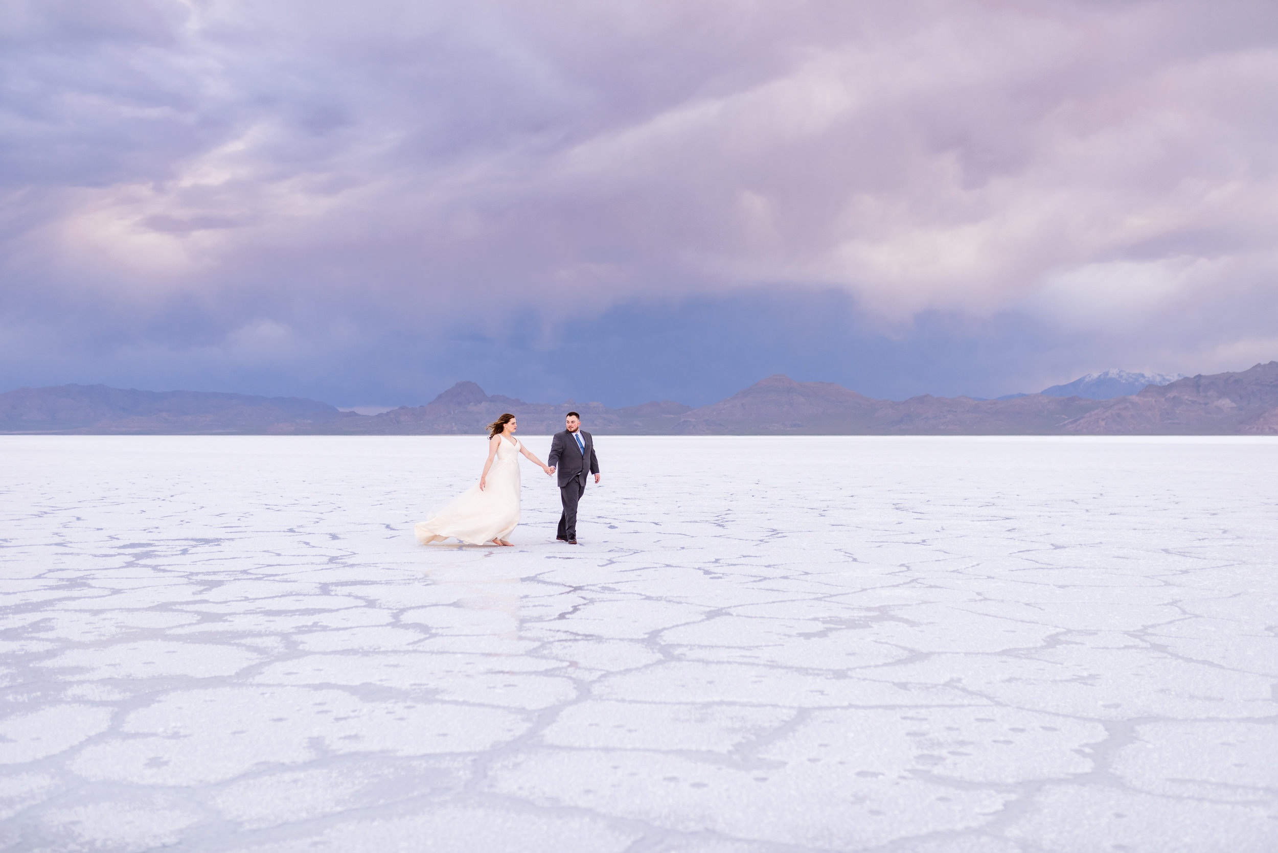 Loving Each other through the storms. Walking pictures of bride and groom. Formals and first look wedding session taken at the Bonneville Salt Flats in Utah during a stormy evening in May. Gold and ivory wedding dress with groom's blue suit and purple tie. Images taken by Coley Cook Photography.