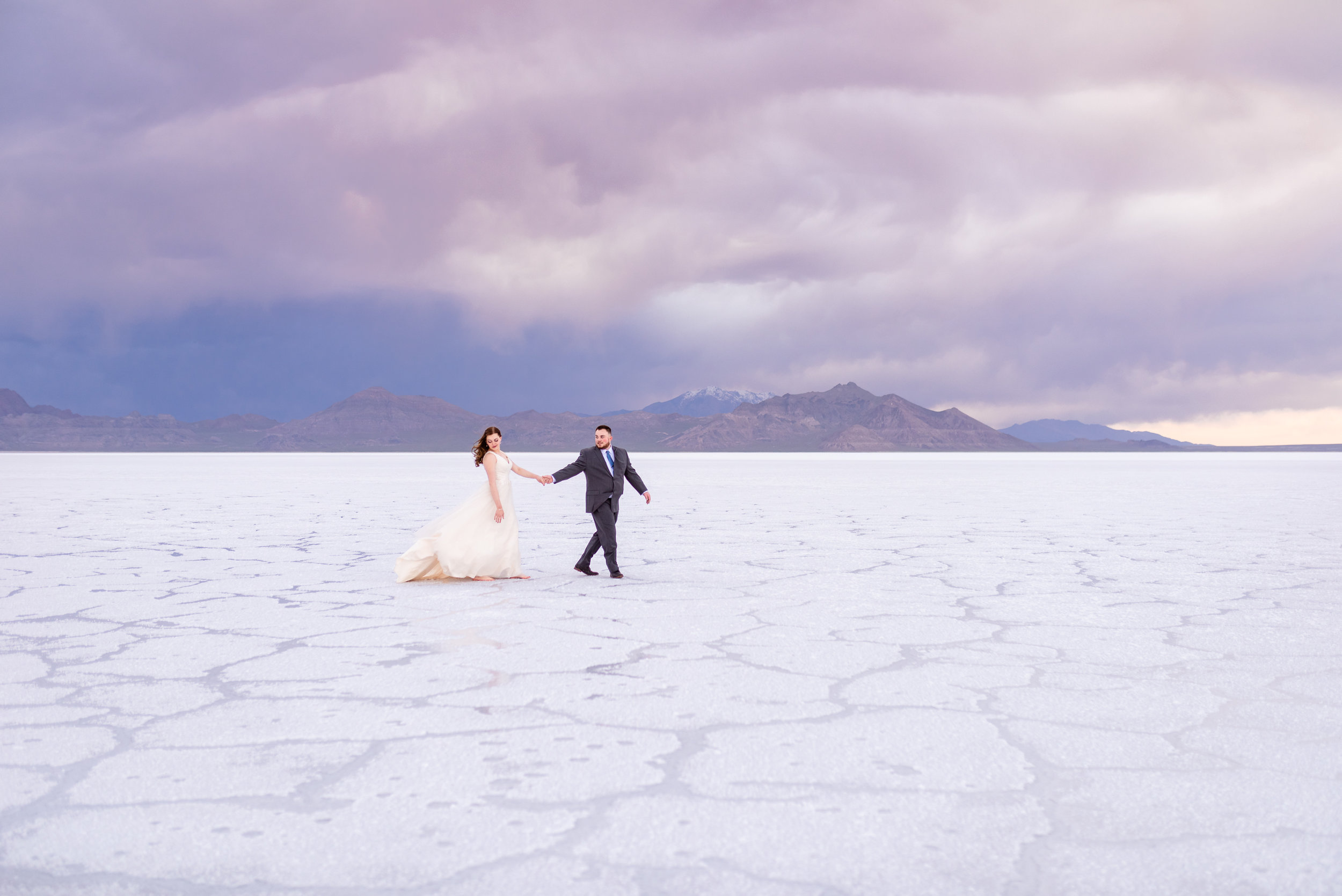 Loving Each other through the storms. Walking bride and groom pictures. Formals and first look wedding session taken at the Bonneville Salt Flats in Utah during a stormy evening in May. Gold and ivory wedding dress with groom's blue suit and purple tie. Images taken by Coley Cook Photography.