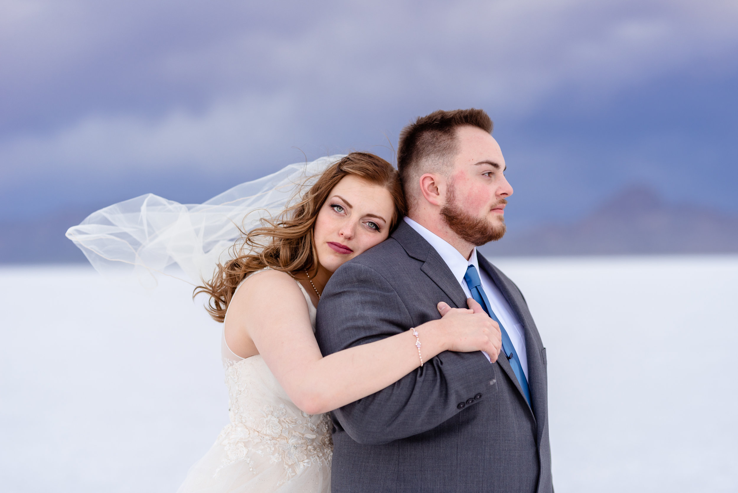 Loving Each other through the storms. Serious faces pose. Formals and first look wedding session taken at the Bonneville Salt Flats in Utah during a stormy evening in May. Gold and ivory wedding dress with groom's blue suit and purple tie. Images taken by Coley Cook Photography.