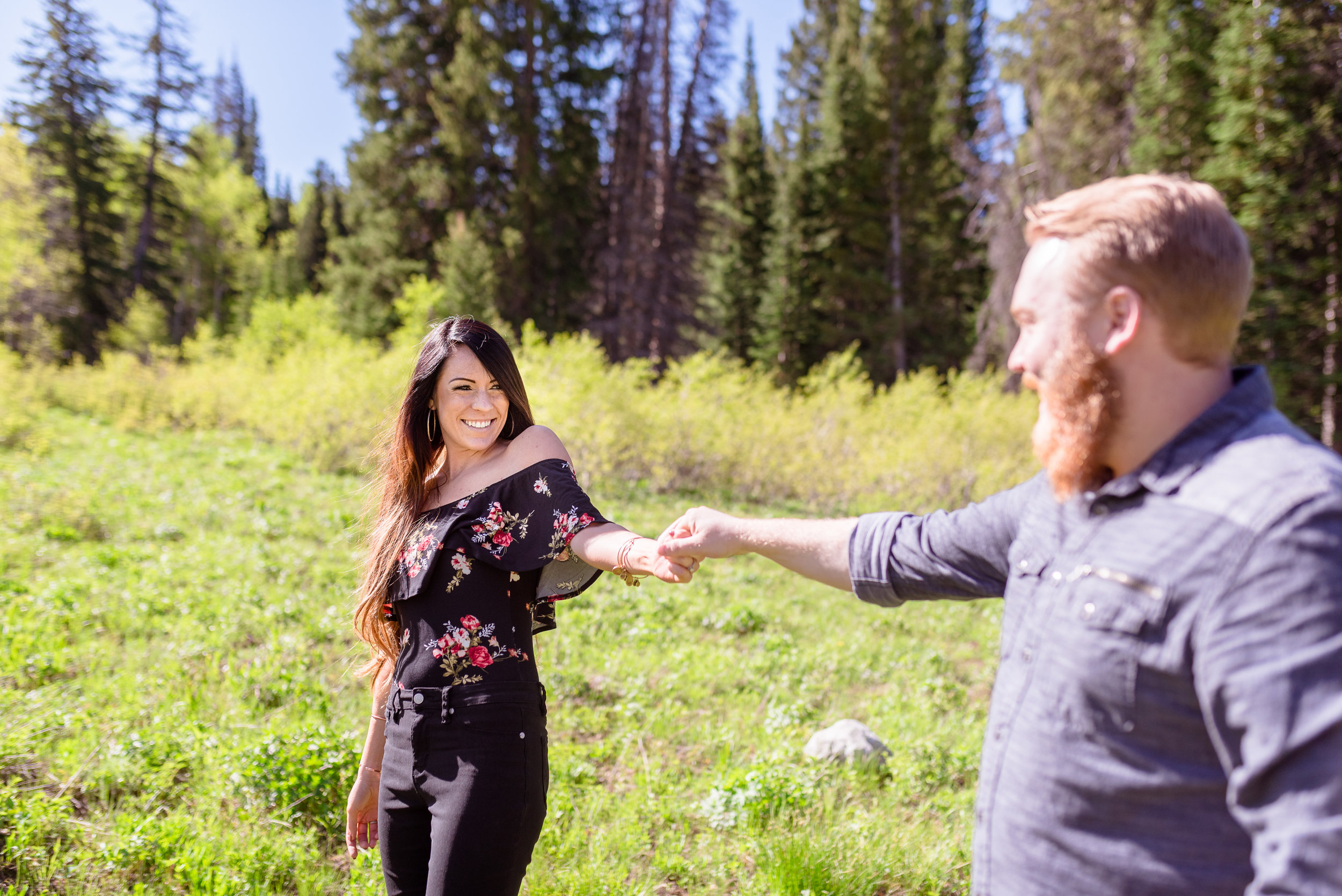 Playfully walking through a meadow during a morning engagement session in the Salt Lake mountains. Engagement session at Jordan Pines Campground in Big Cottonwood Canyon.