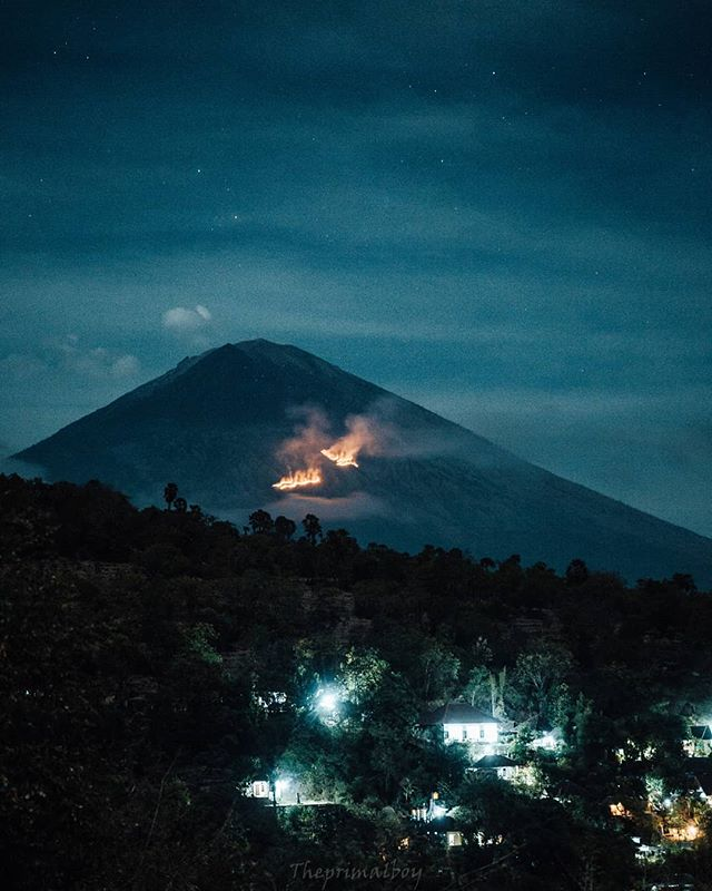 """This is Mt Agung, Bali's biggest mountain (and an active volcano) just hours after it's eruption.. Crazy, right?  Even though we headed straight to the line of fire when news of the eruption hit, we still arrived hours after. Hoping to see lava rocks and flames spewing everywhere, we jumped in the car with Kadek, our Indonesian friend. Then we embarked on a spontaneous 2 1/2 hour drive through the winding, high roads of Bali. .  We searched high and low for the perfect view. """"Amed"""" - Kadek told us. """"This, is where we will get the best view."""" A beautiful beach side community known for its snorkeling, surfing and views of agung. We finally arrived around 2 am and settled on a tiny little bamboo platform drinking local wine just off a cliff, overlooking Mount Agung.. @balidaily . . . #mindfulness #portraitkillers #pursuitofportraits #makeportraitsnotwar #chasingportraits #postthepeople #visualgang #agameoftones #portraitgames #createexploretakeover #folkportraits #rsa_portraits #portraitmood #portrait_shots #canon #theportraitpr0ject #pr0ject_uno #pr0ject_soul #thedarkpr0ject #themysterypr0ject #sombrebeings #humanedge"""