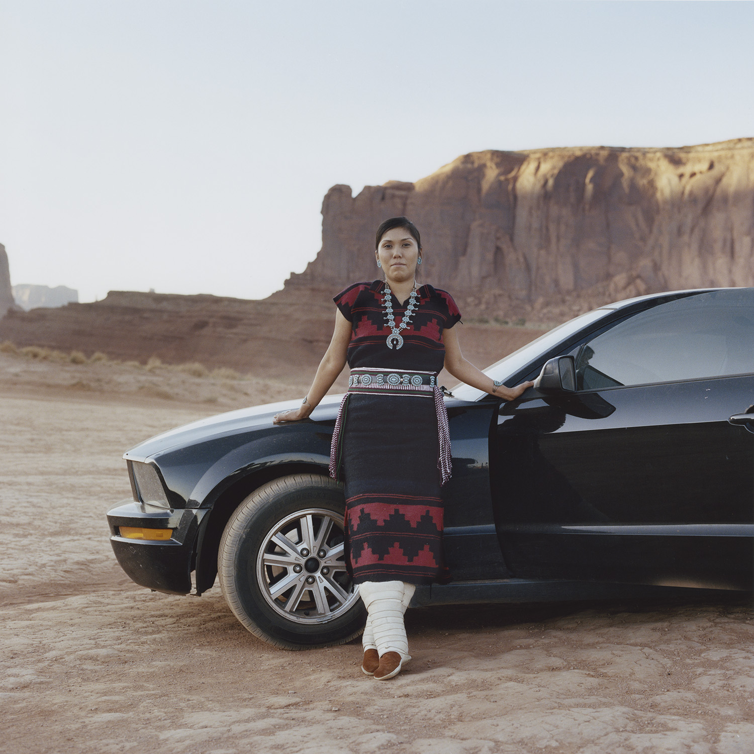 Everita and her Mustang ©Carlotta Cardana  A posed portrait of Evereta Thinn, 30 at the time the picture was taken. She works as an administrator at School District on the Navajo Nation and aspires to start a language and cultural immersion school for the Diné (Navajo) people. She is photographed in Monument Valley, where part of her family lives, with her Ford Mustang. The car was given to her as a present by her brother, who passed away shortly afterward; it became her most cherished possession and a way of honoring her brother's memory