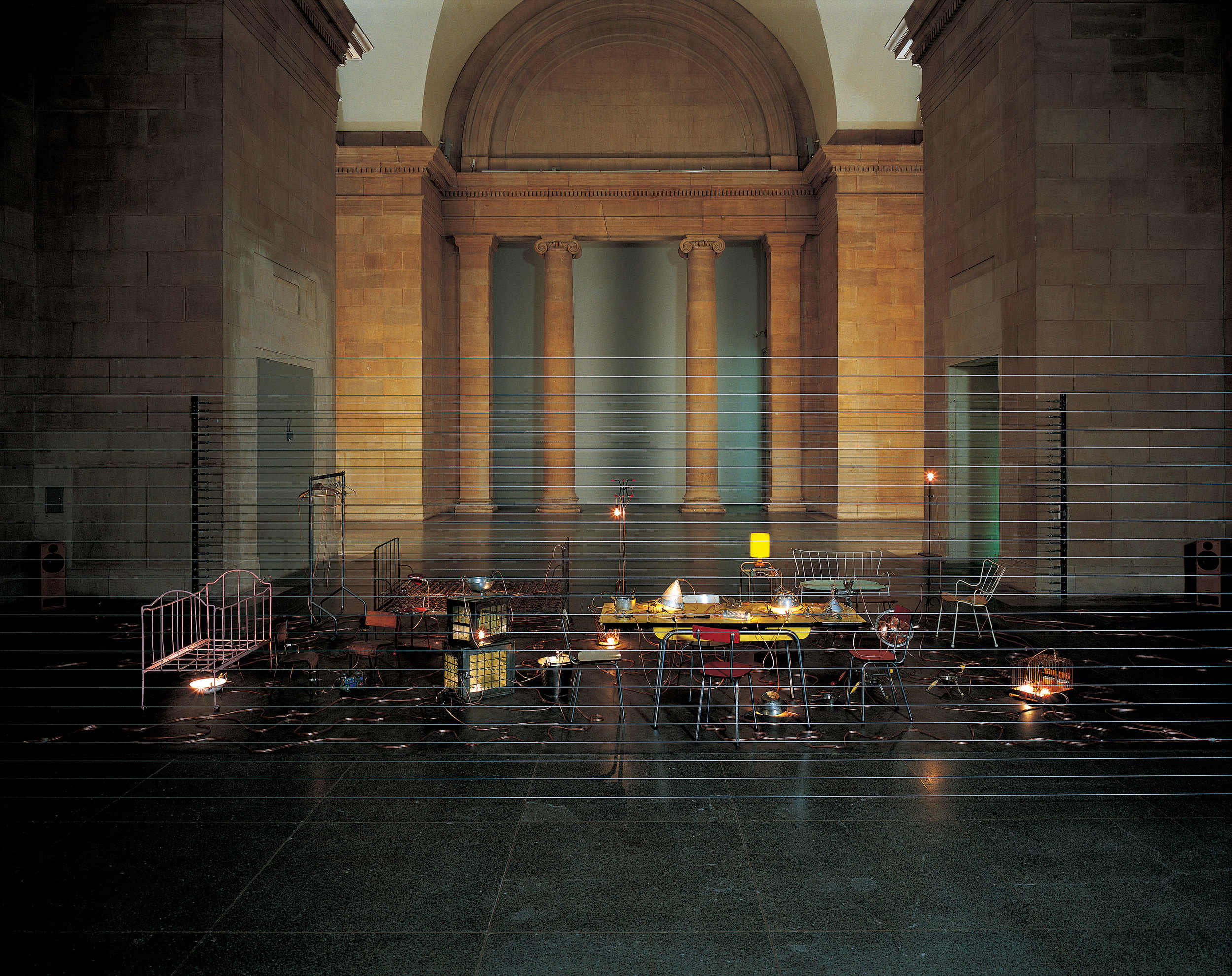 Homebound (2000) Mona Hatoum, mixed-media installation with kitchen utensils, furniture, electric wire, light bulbs, computerized dimmer unit, amplifier and speakers. Installation view at Duveen Galleries in Tate Britain, London, 2000. Photo by Edward Woodman. Courtesy the artist and Galleria Continua, San Gimignano/Beijing/Le Moulin.