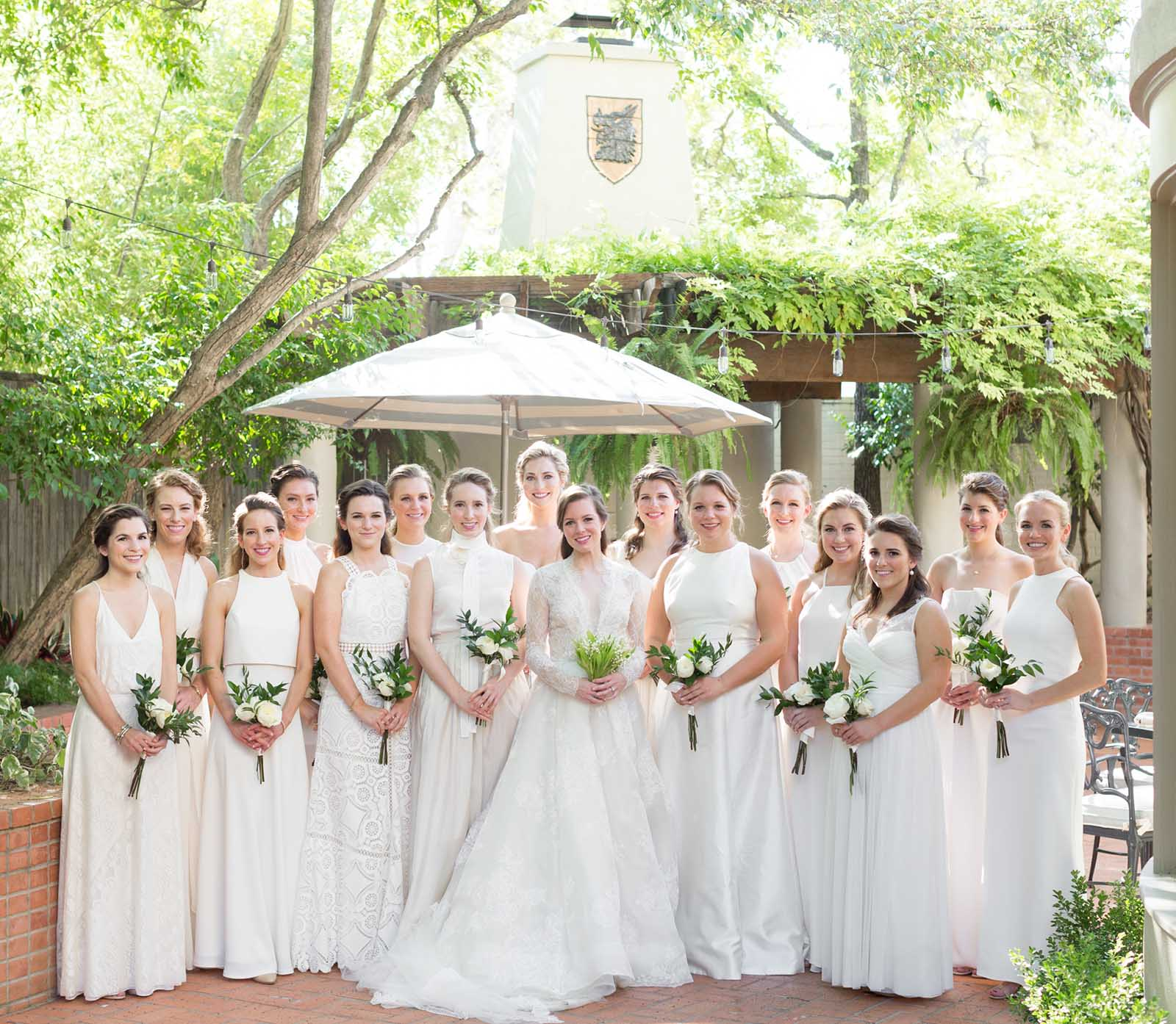 A bridal party gathered together in a court yard in San Antonino, Texas. They are wearing all white and carrying lilies.
