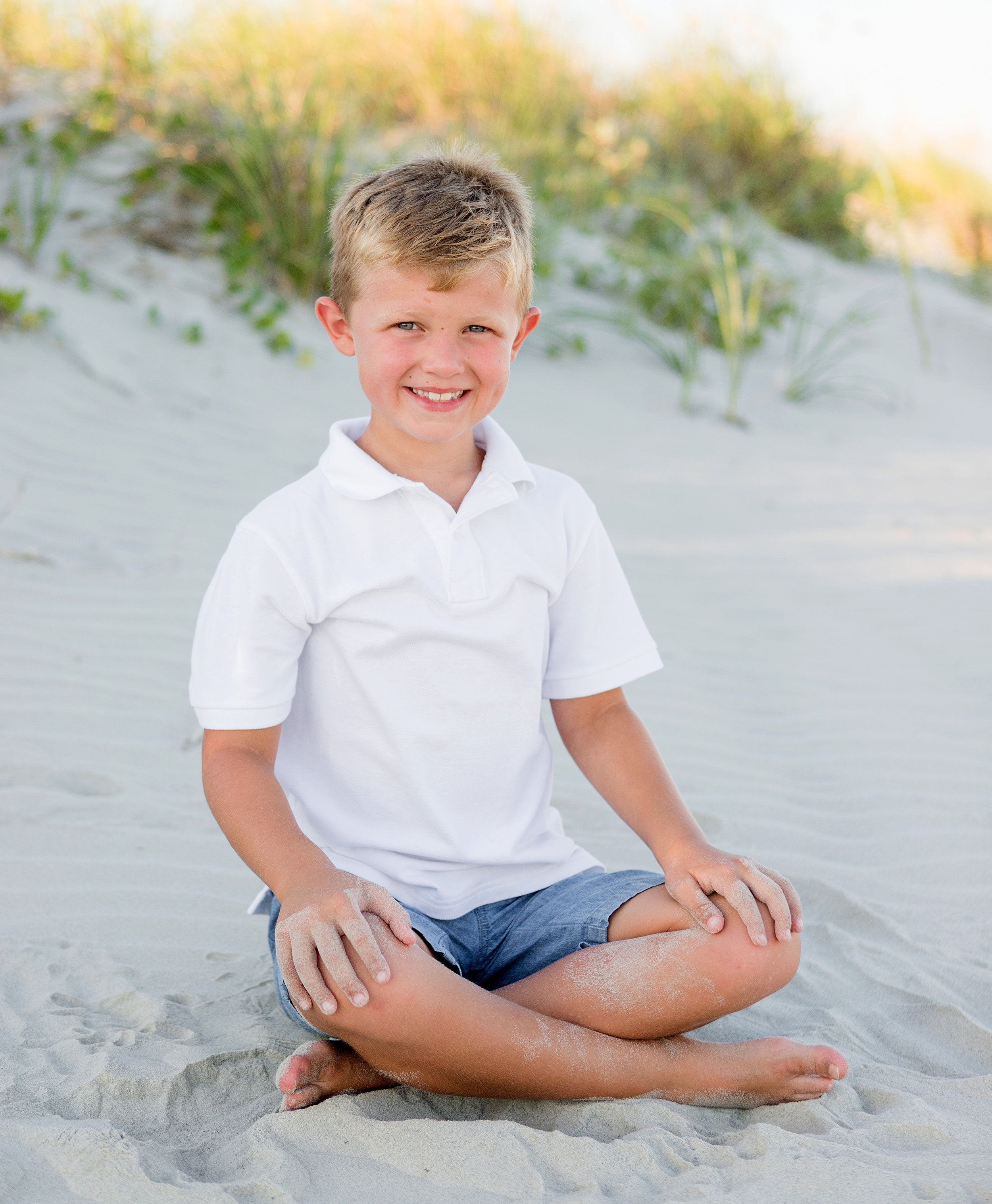 little boy sitting in the sand during a family portrait sitting on the Isle of Palms in Charleston, SC