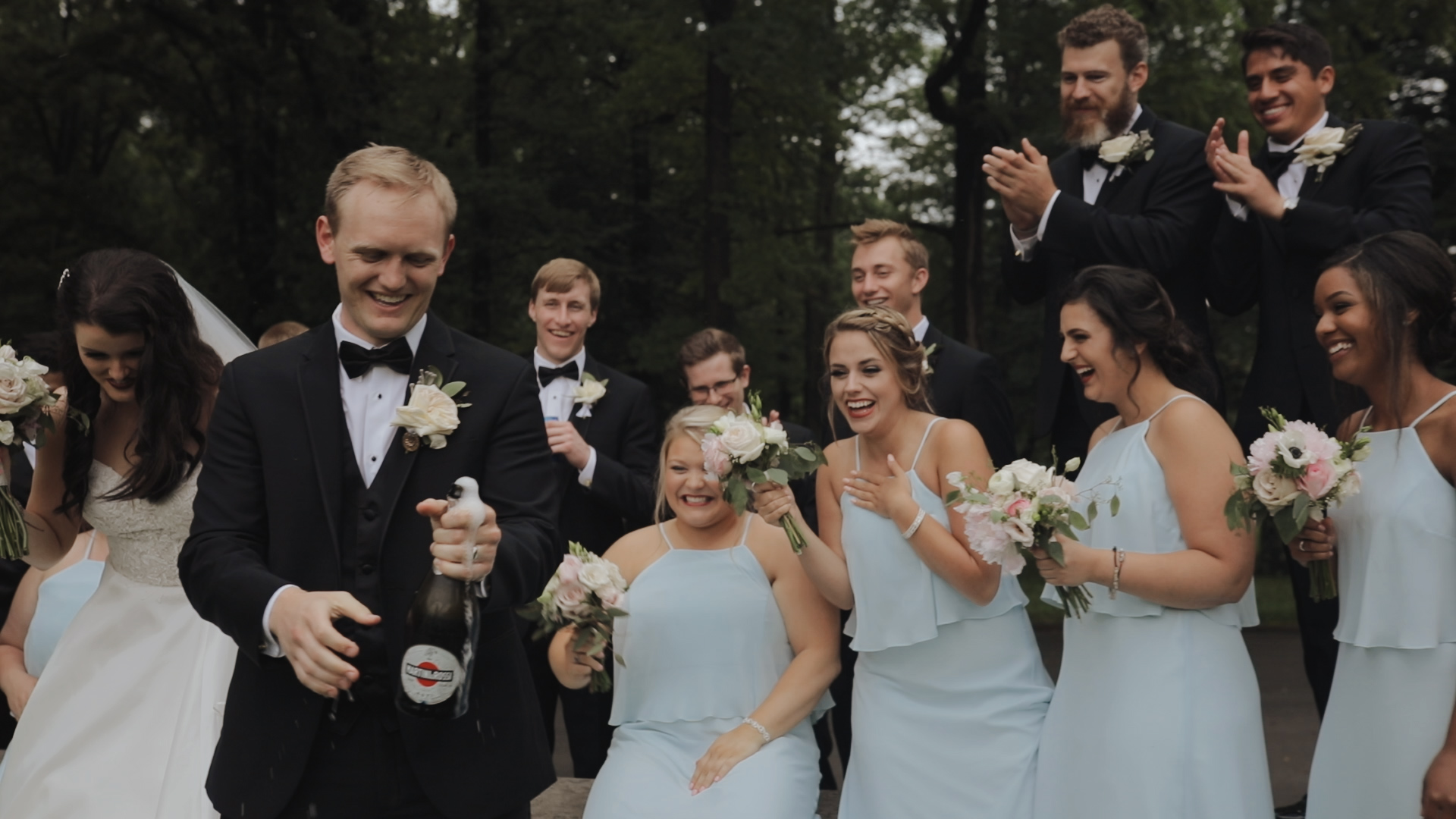 Groom popping champagne at wedding wedding party cheering in background wearing Hayley Paige Occasions soft blue bridesmaids dresses