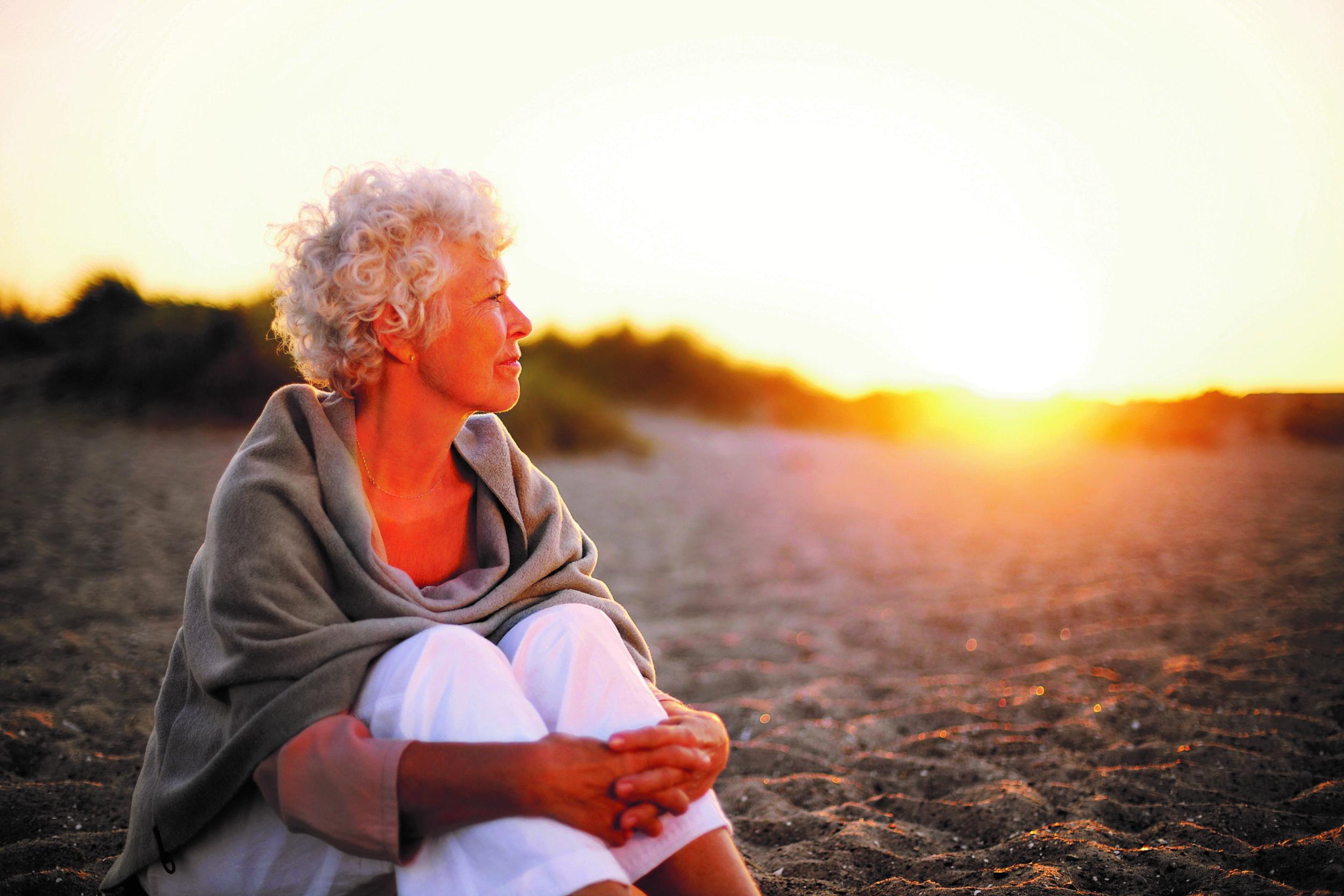 bigstock-Old-Woman-Sitting-On-The-Beach-62840824.jpg