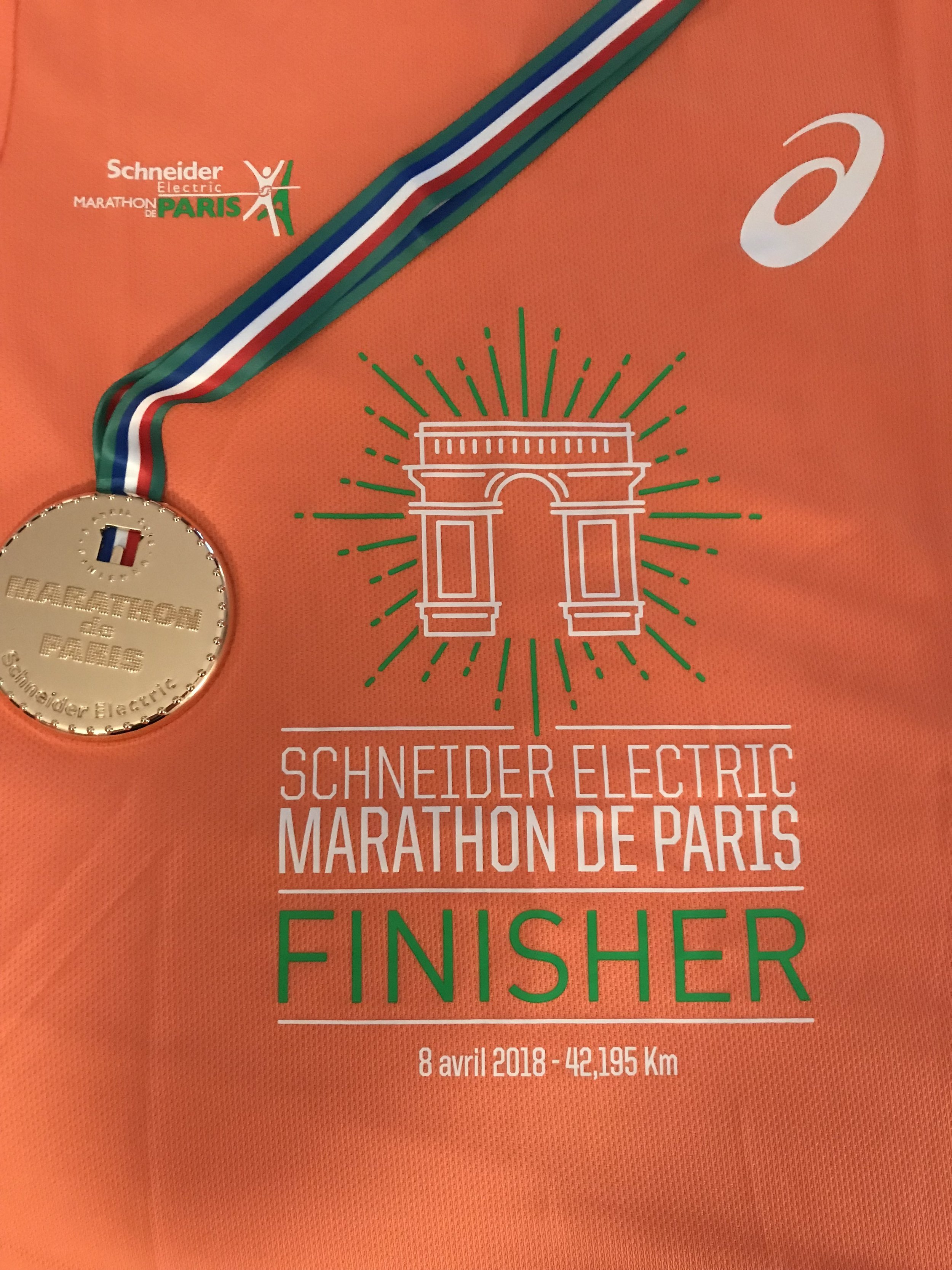 The race bling and finisher's Asics technical tee. Each of the studs on the medal represent a kilometre, so there are 42 dots on the medal.