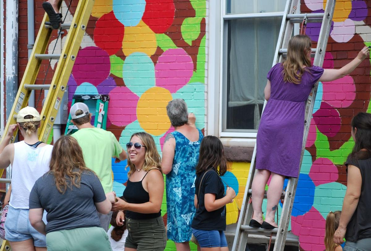 """BERKS-MONT - Kutztown residents helped paint a community mural on the exterior of Betty's on Main Street as part of the Ten Thousand Flowers Project.""""Our goal is to keep a sustainable town and make it more livable with holistic endeavors and community building projects. We have beautification initiatives so this is one. The whole idea of it being flowers ties in with our native plant garden,"""" said Kutztown Thriving chair Caecilia Holt…"""