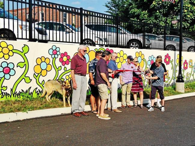 """NEWS-HERALD - """"So far in Perkasie, we have 99 flowers,"""" said Tim Gibson, the artist who came up with the idea for the Ten Thousand Flowers Project.Those 99 flowers are drawn on a mural in three different places in the borough — a retaining wall behind borough hall, Chimayo Gallery and Threddies.The next step is to arrange to paint other sections of about 100 flowers each in about 100 other small towns across the country, then a return to Perkasie to finish up the project by painting the 10,000th and final flower here…"""