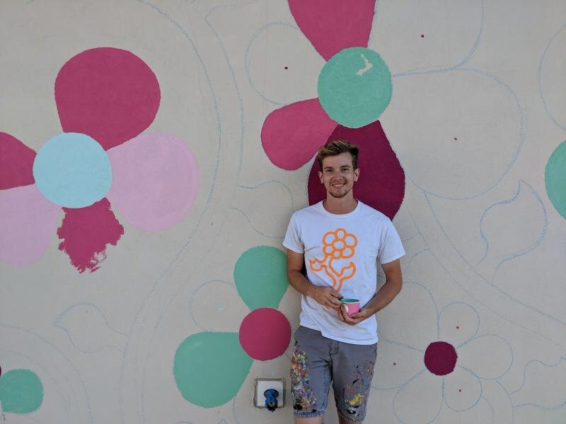 CAPE GAZETTE - In 2018, Tim Gibson, an artist from Pennsylvania, embarked on a mission. He converted a small bus into a traveling home and set out with one goal: to paint more than 10,000 flowers in the United States. But this isn't a solo project. In every town Gibson visits, he calls for the community to come out and help him. Gibson sets up a mural, outlines the flowers, and allows everyone to join in to paint them. Each mural features a jigsaw effect, creating one singular painting stretching across the country…