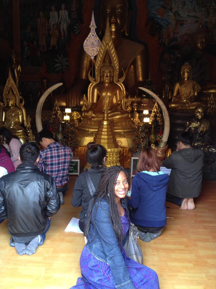 Sitting inside of a temple at Wat Prathat Doi Suthep.  Everyone is careful to not point their feet in the direction of the Buddha Statue