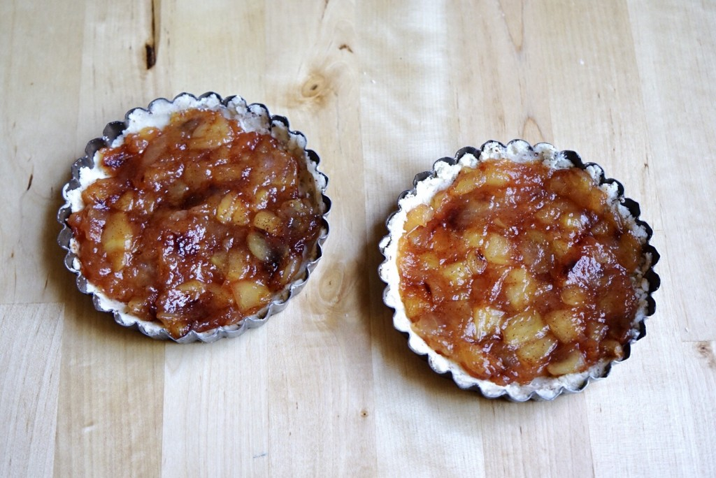 Arrange the cooked apples in the mini tart pans.