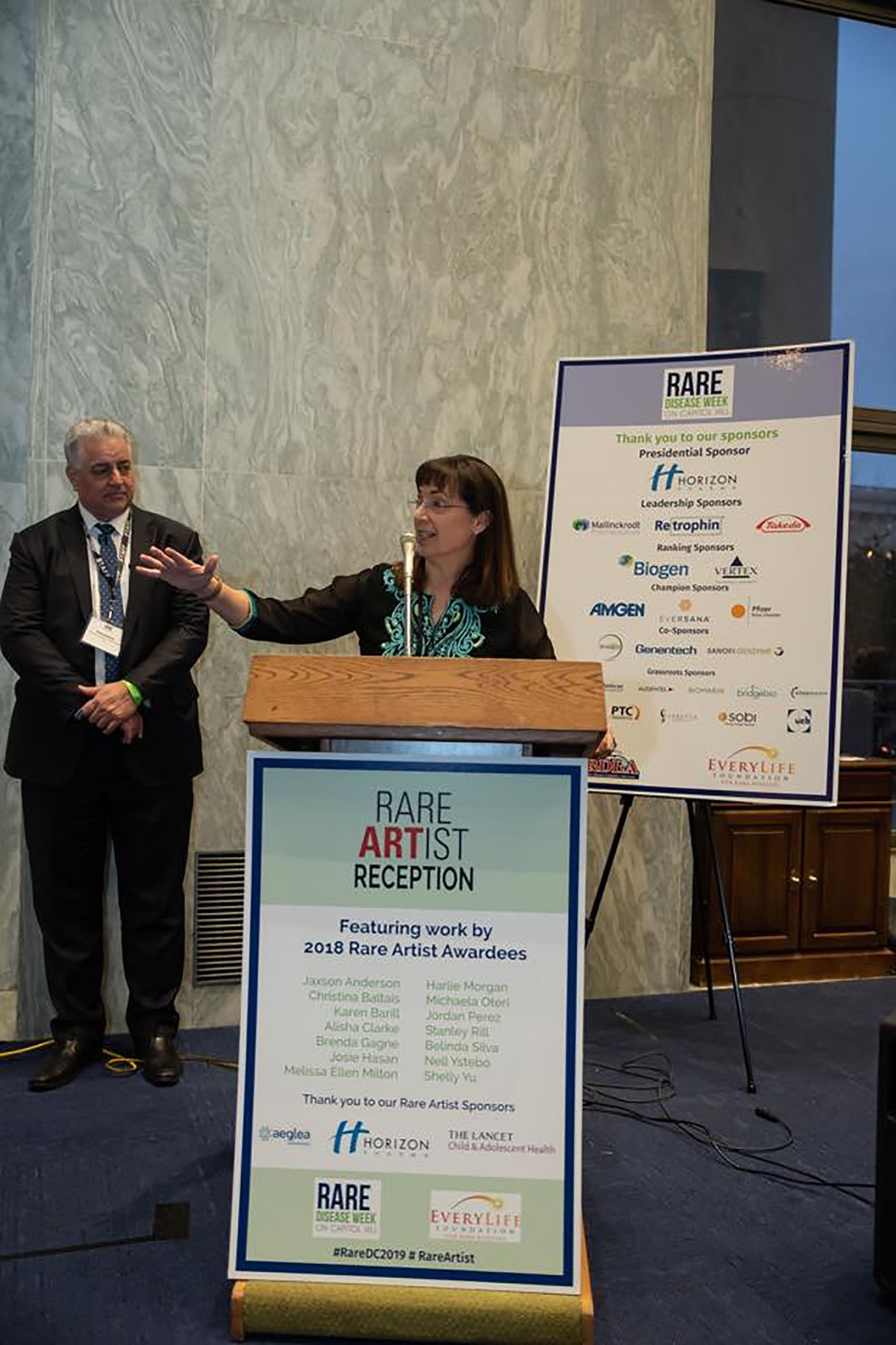 "Addressing the audience at the Rare Artist Award Reception, February 2019, in Washington, DC. They asked award winners to keep the speeches to two minutes. I grinned and said ""No problem, I can only stand up for 5."" As you can see, I am one of those people who cannot seem to speak without gesturing with their hands. :-)  The Rare Artist annual competition is for artists with rare diseases. Its purpose is to raise awareness for those rare diseases which oftentimes get overlooked when it comes to medical research and physician education. My art piece ""Flora & Fauna"" was among 350 entries. I felt very honored to be among the eight artists selected for an Award. This was me doing my bit to help raise awareness for my rare disease of Dysautonomia."